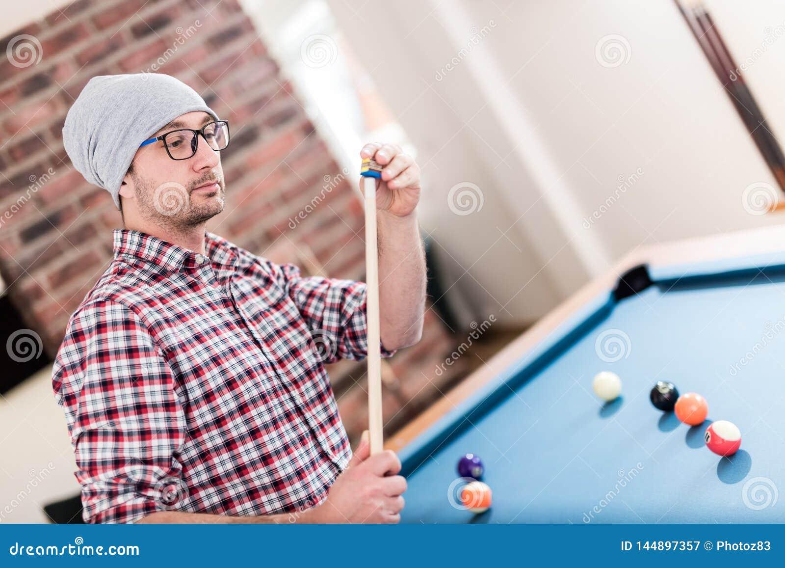 Den trendiga hipstermannen torkar en stickreplik med krita, medan förbereda sig för det nästa slaget