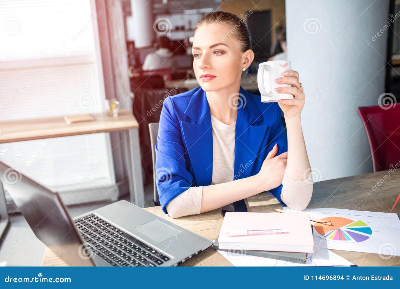 Den trevliga och attraktiva flickan sitter på tabellen och dricker te Hon ser till fönstret och att drömma Denna vuxen människa h