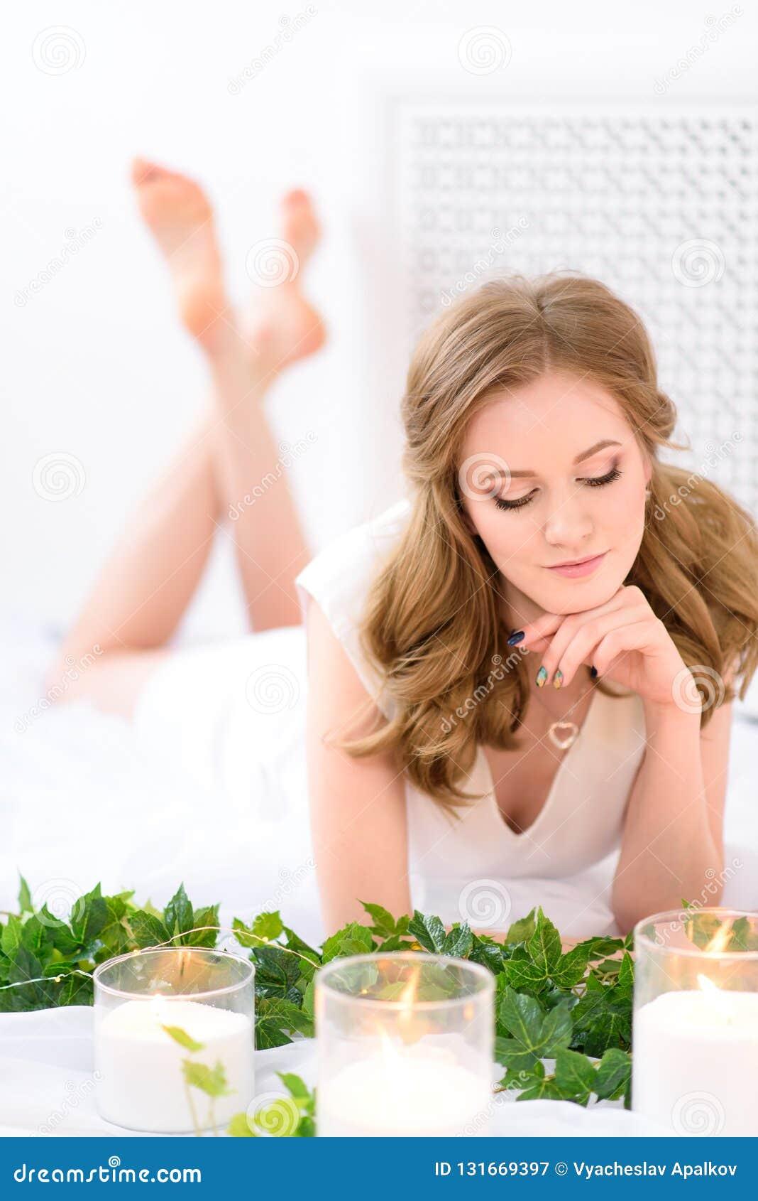 Den trevliga unga damen som försiktigt ligger i ett rent ljust vitt rum, ögon rymde ner shyly Ursnygg ung brunettkvinna med i en