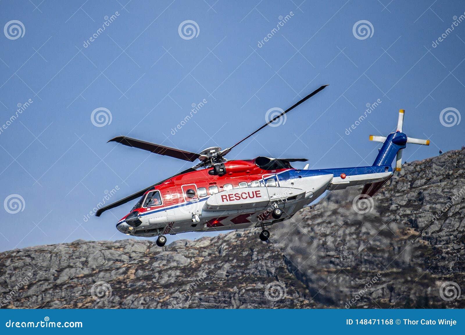 Den Tricolor räddningsaktionhelikoptern i rött, vitt och blått kommer ner för att landa