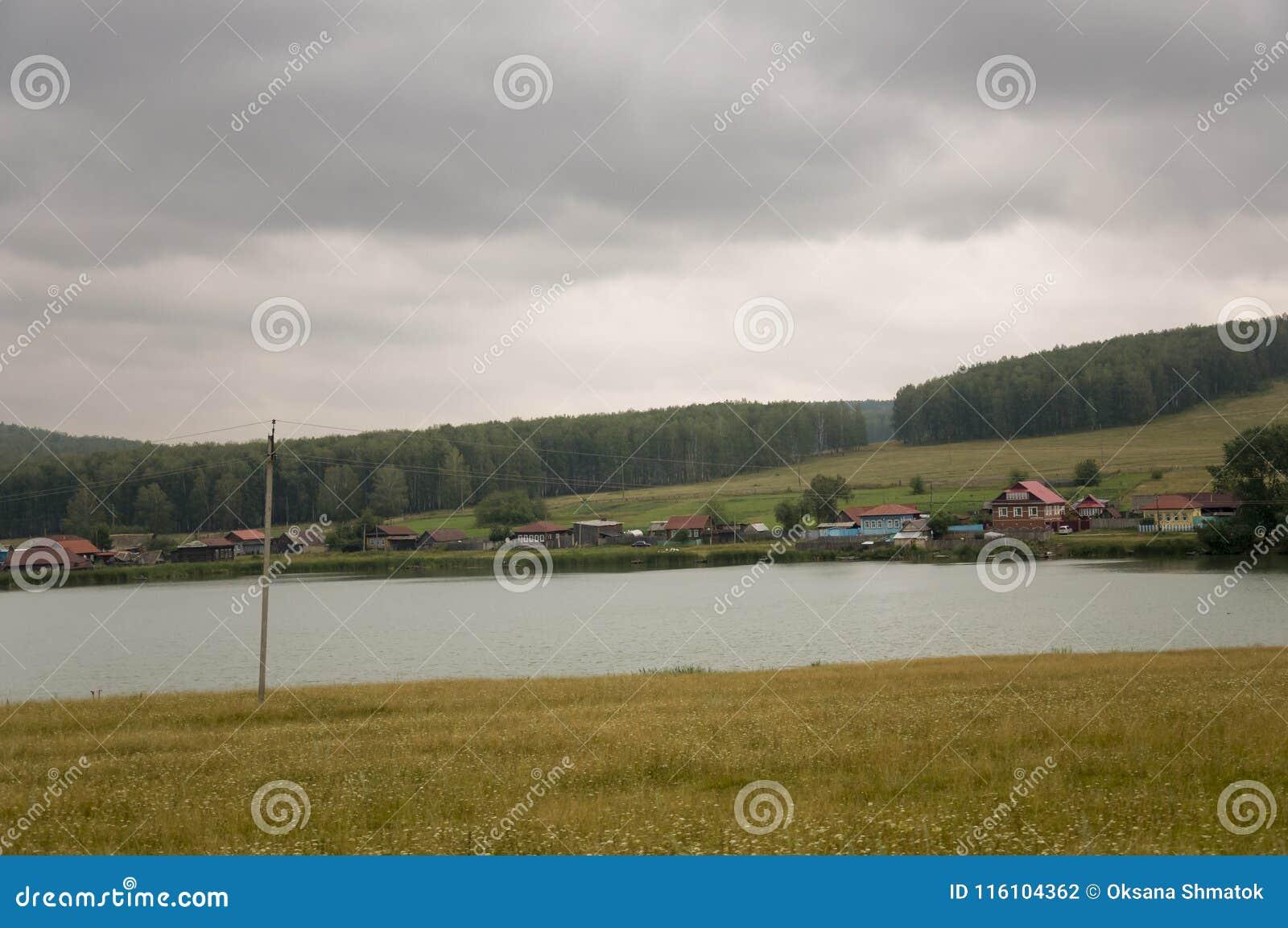 Den tunga grå färgen fördunklar i den kalla hösthimlen över by med små hus som är långväga i bergen och fälten Små flodflöden