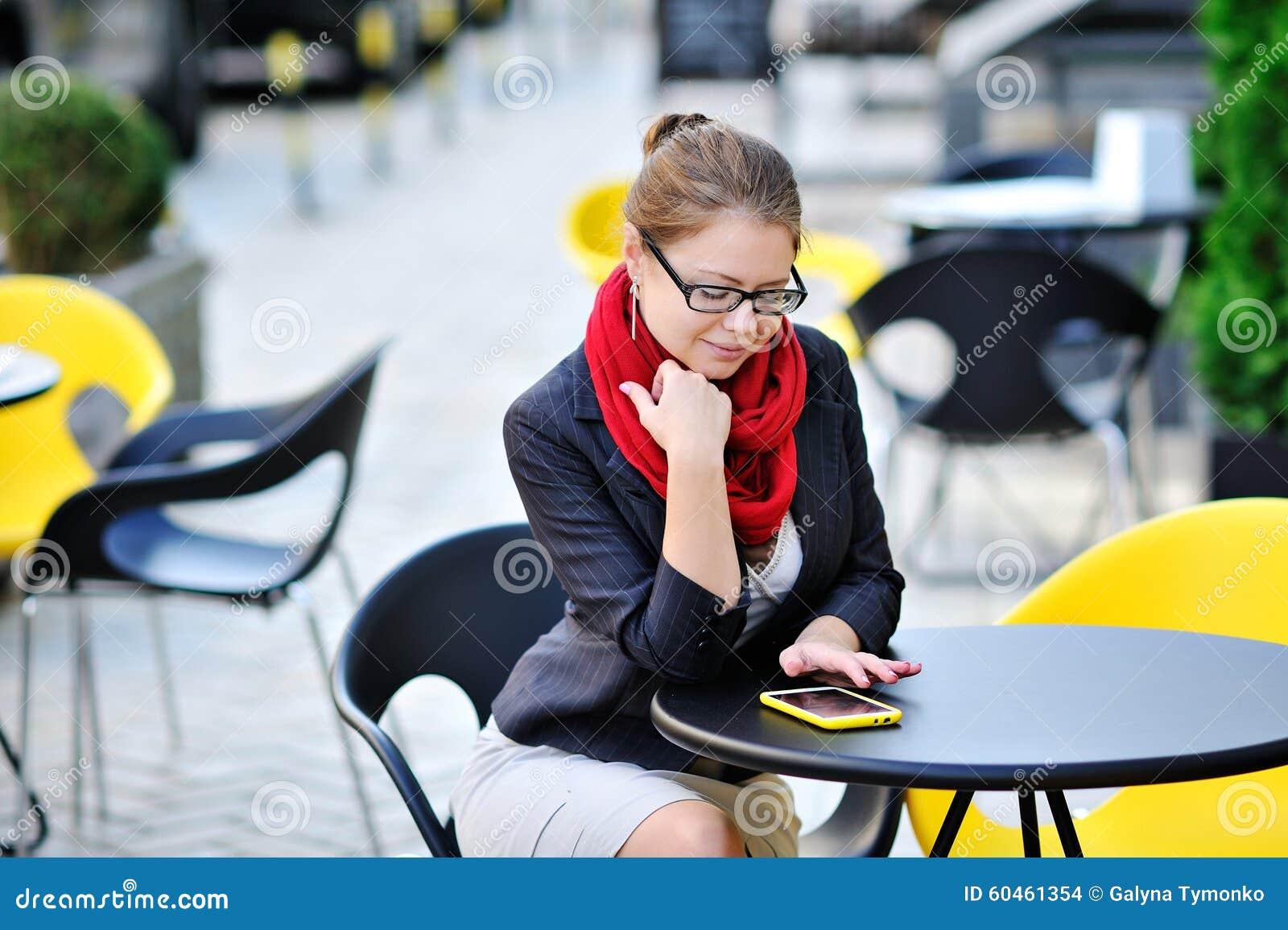 Den unga affärskvinnan använder den smarta telefonen för arbete i kafé