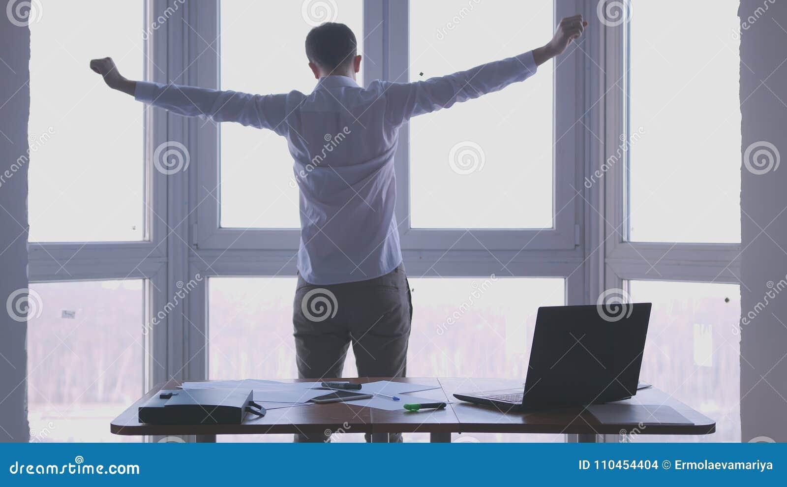 Den unga affärsmannen beundrar sikt från fönstret fördelade ut hans armar i ett kontor