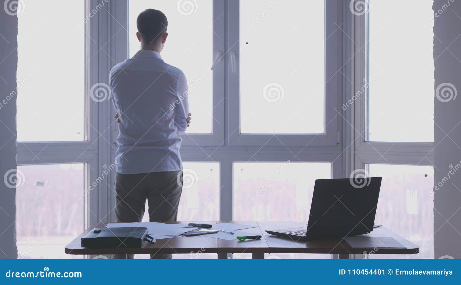 Den unga affärsmannen beundrar sikt från fönstret i ett kontor