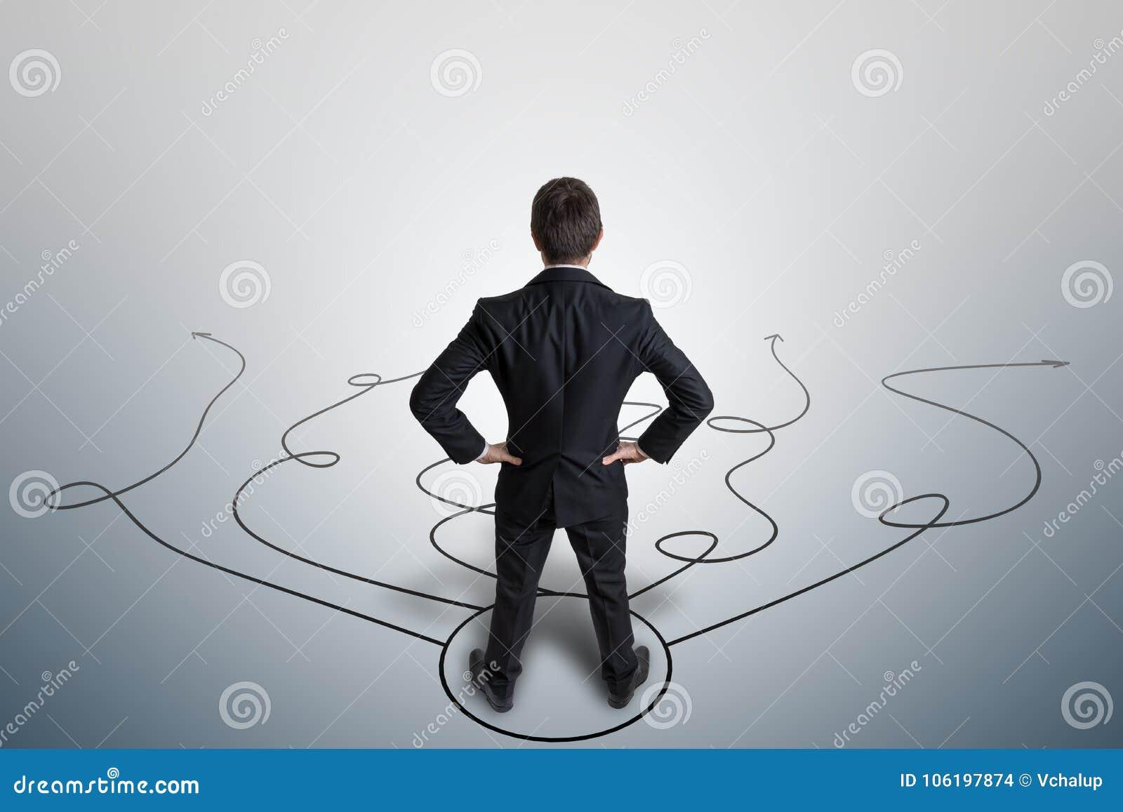 Den unga affärsmannen gör beslut och väljer strategi Beskåda bakifrån