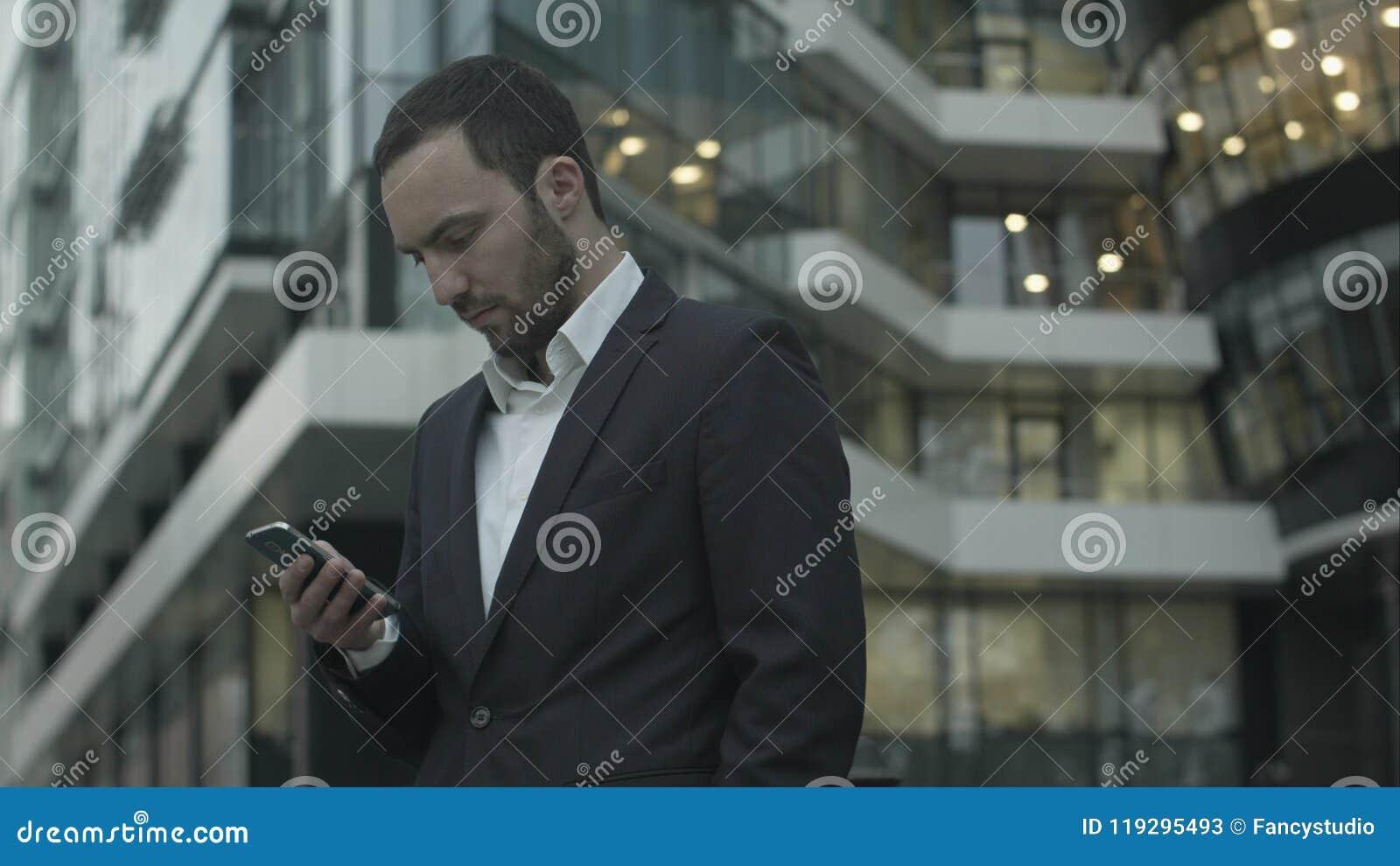 Den unga affärsmannen läser ett anseende för textmeddelande utanför kontoret