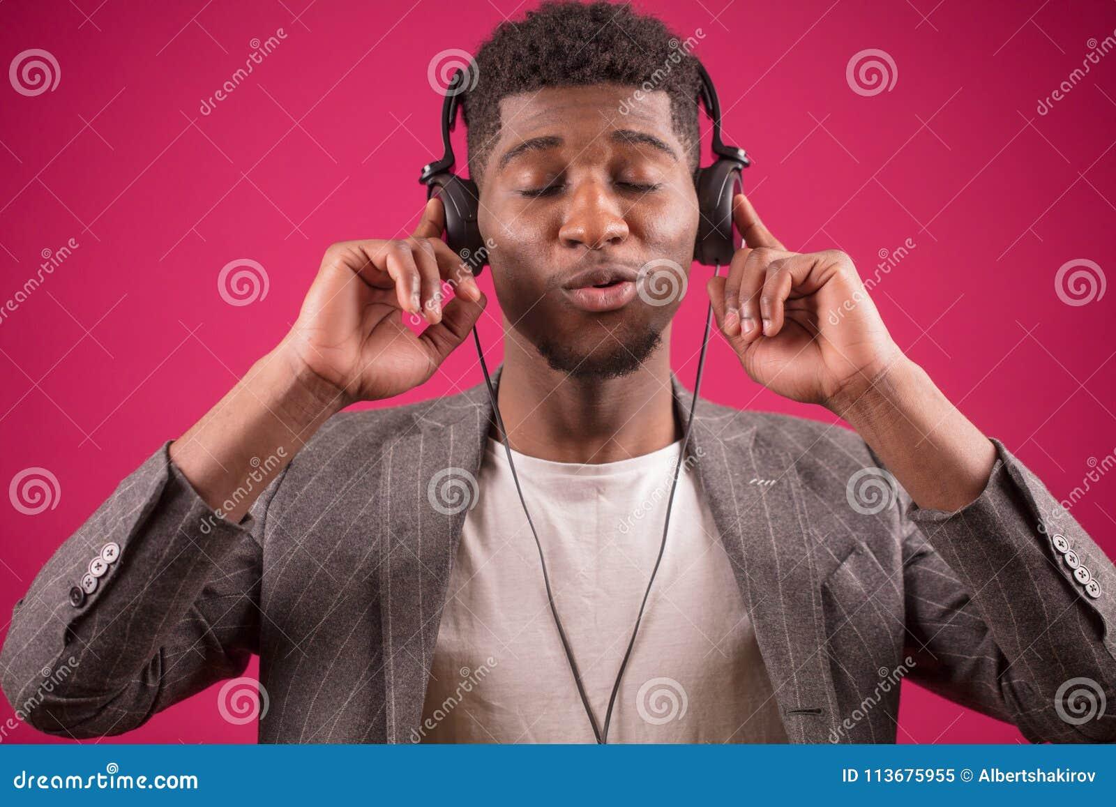 Den unga afrikanska mannen som bär hörlurar, är tokig på musik