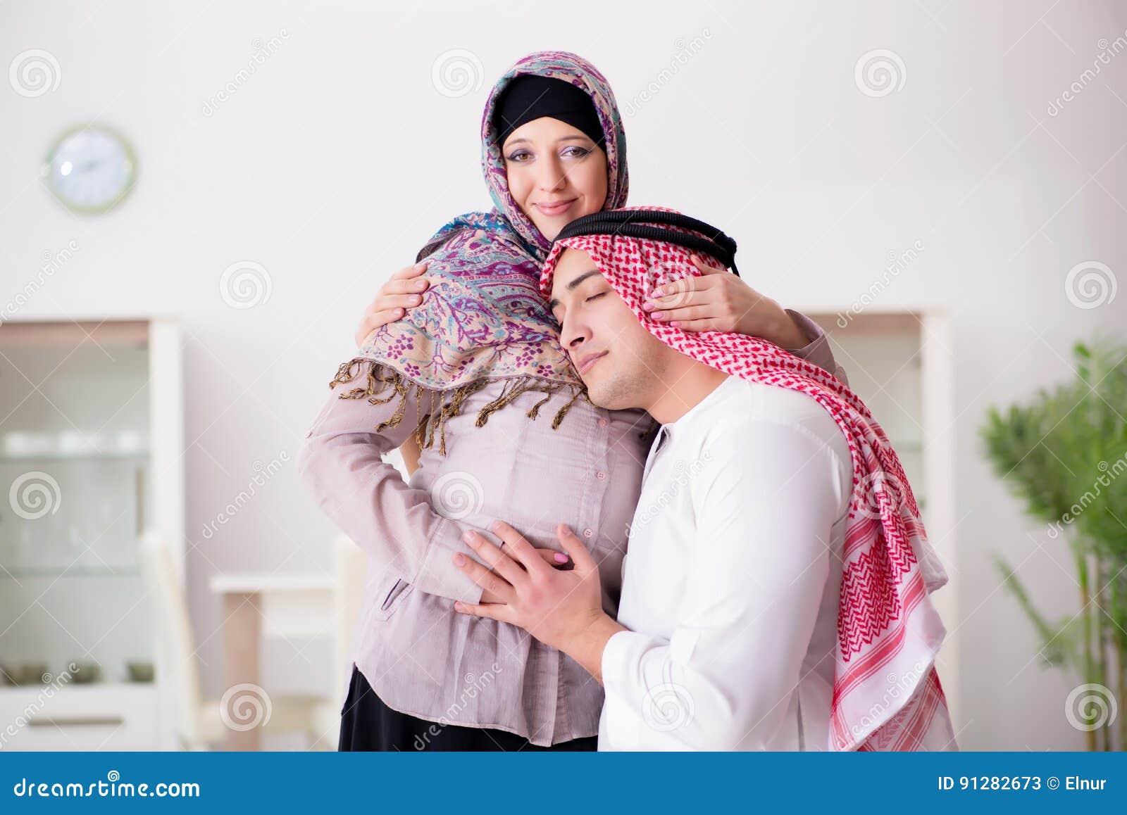 Den unga arabiska muslimfamiljen med den gravida frun som förväntar, behandla som ett barn
