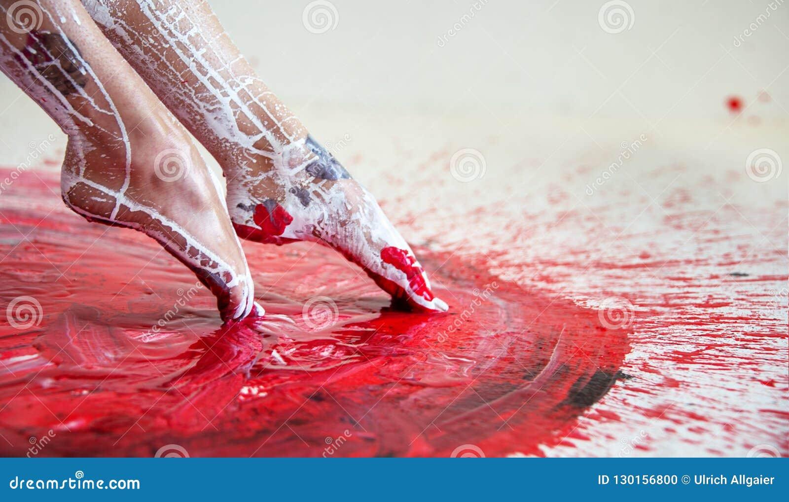 Den unga artistically abstrakta målade kvinnaballerina med svart röd vit, målarfärg, petar hennes fot i röd målarfärg, idérik kro