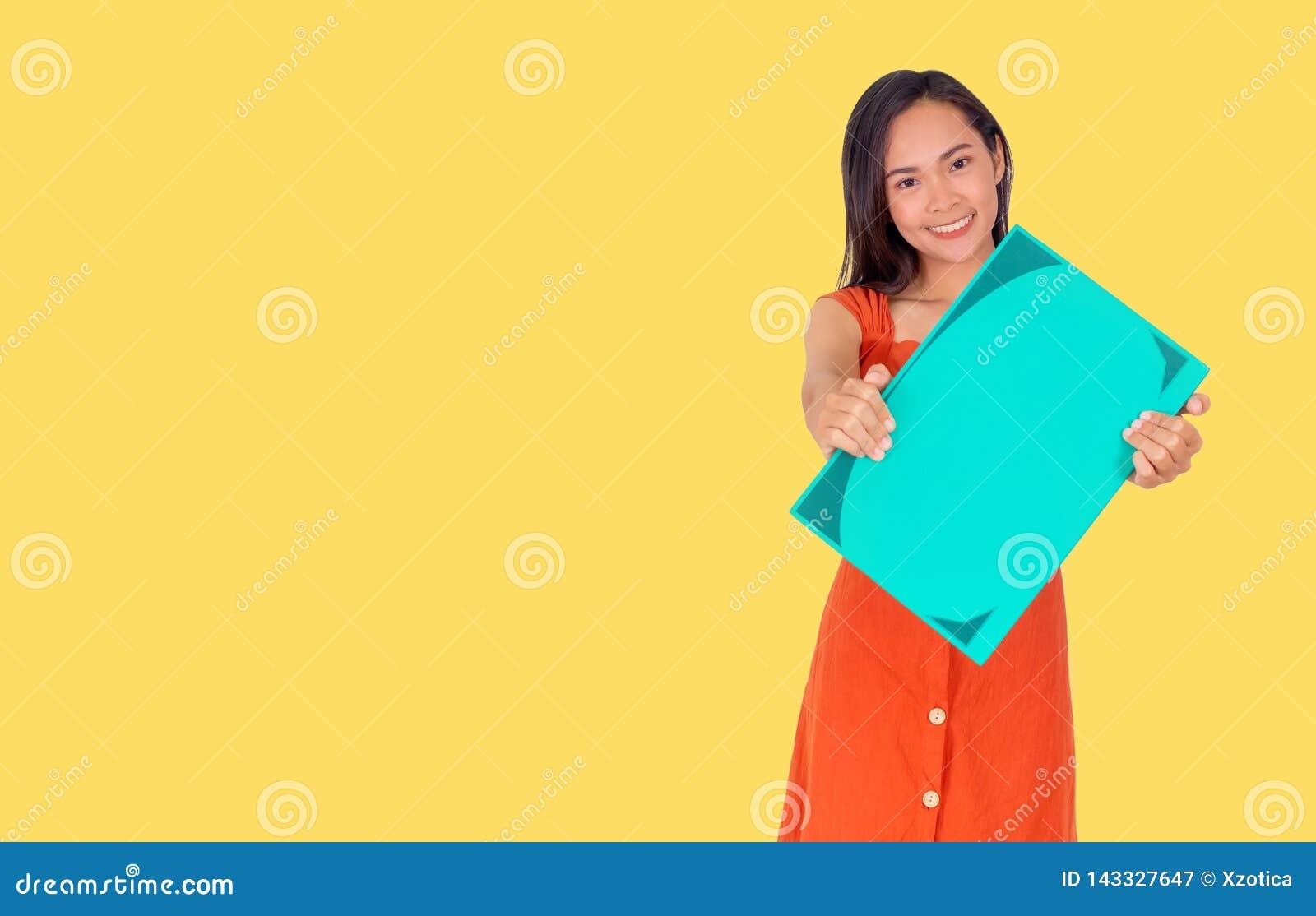 Den unga asiatiska flickan i orange klänning visar en stor grön bok till den gula bakgrunden för kameran