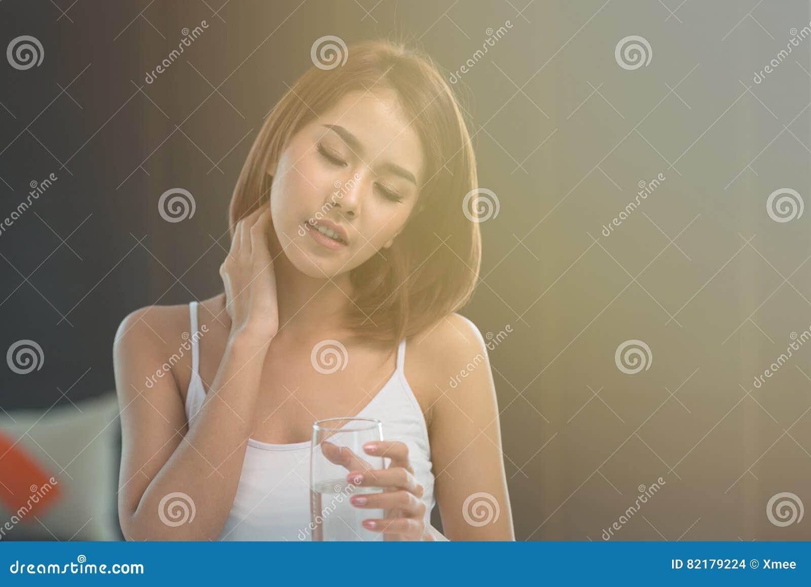 Den unga asiatiska kvinnan har en smärta i halsen