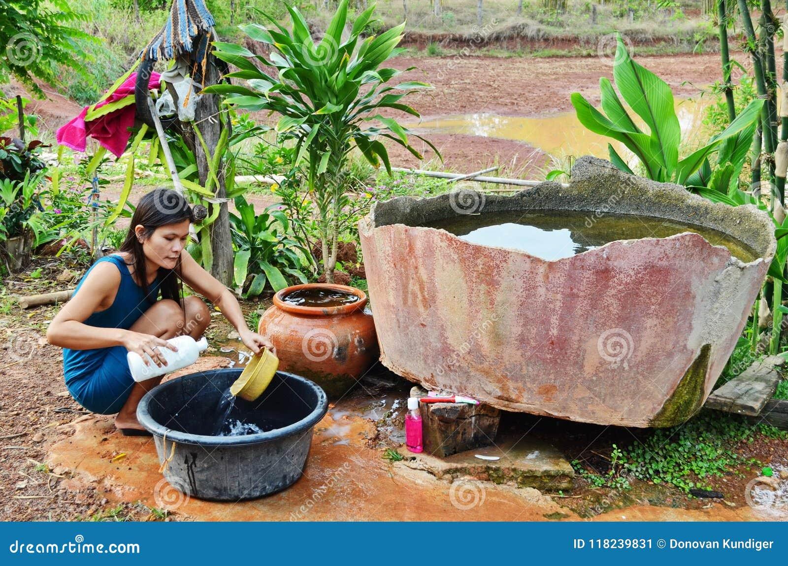 Den unga asiatiska modern tvättar disk i primitivt kök