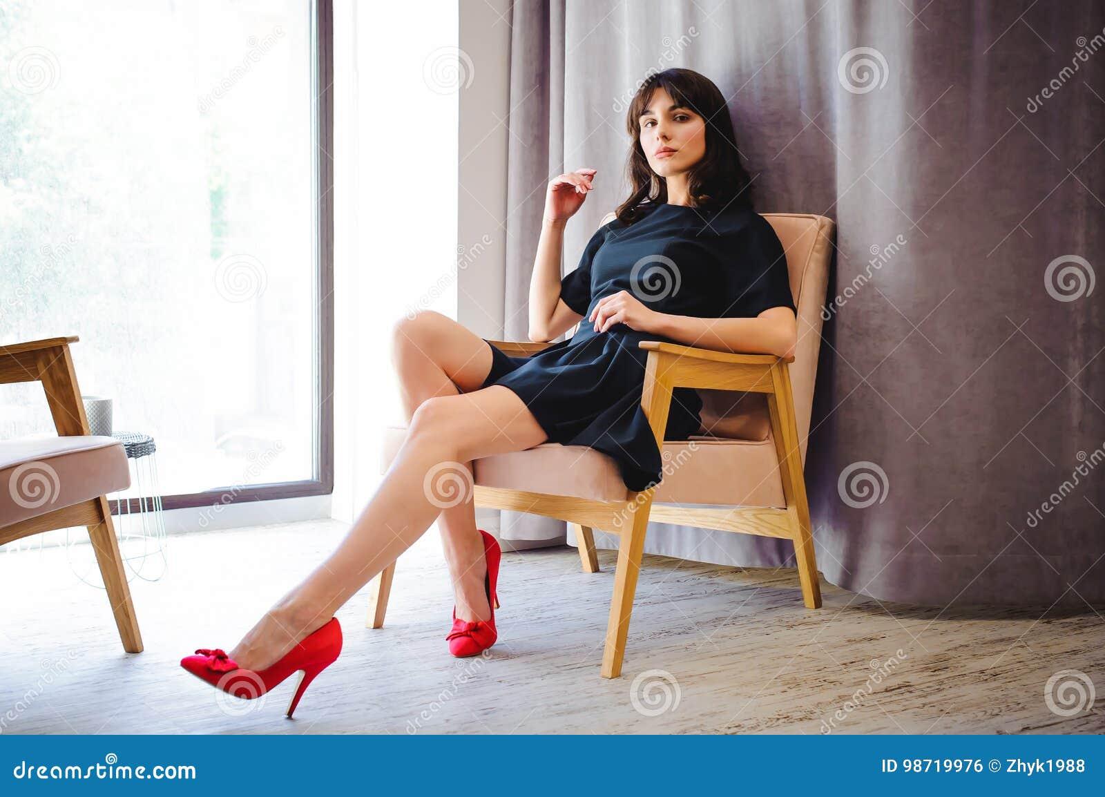 Den unga attraktiva kvinnan med långa ben i svart elegant klänning, sitter i stol nära fönster i inre av rum