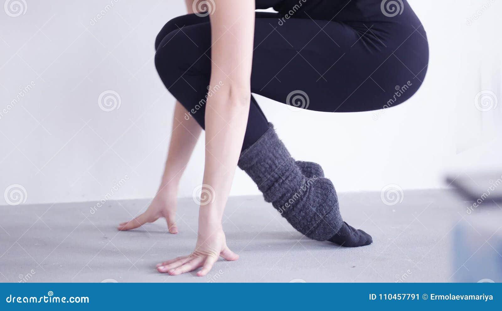 Den unga behagfulla ballerinafotnärbilden i damaskerlöneförhöjningar på sockor på en bakgrund av den vita väggen utbildar i studi