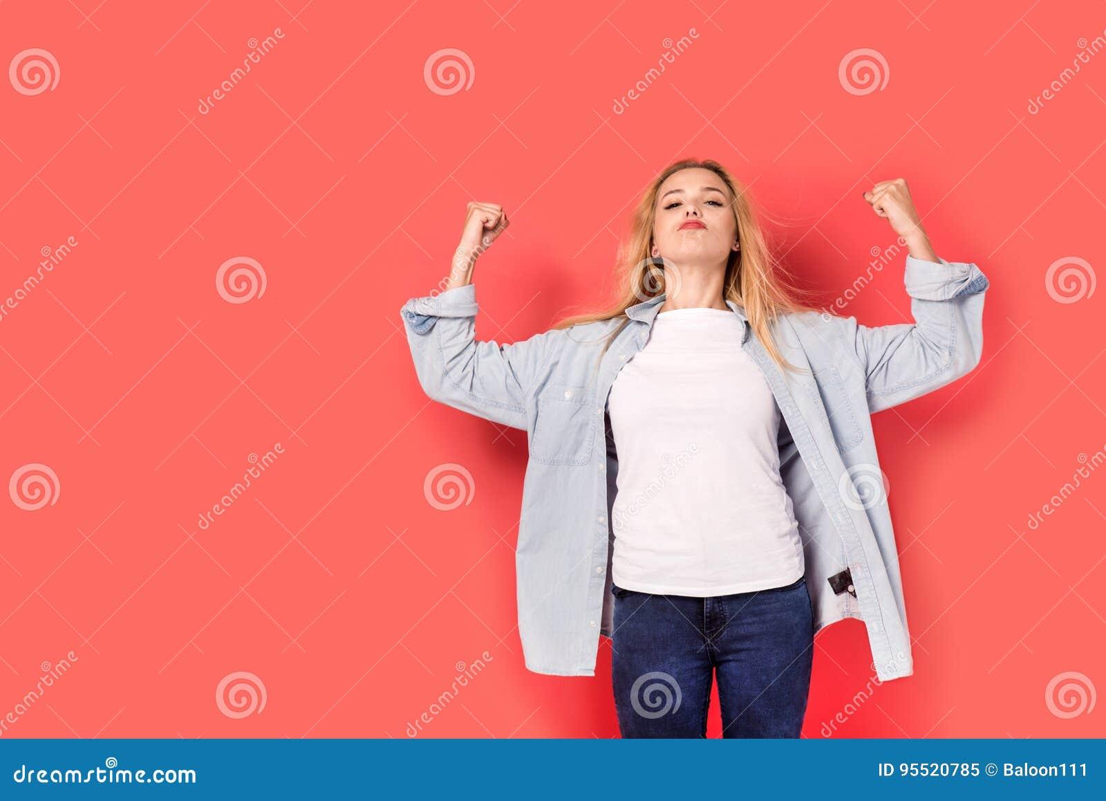 Den unga blonda flickan visar henne styrka på röd bakgrund