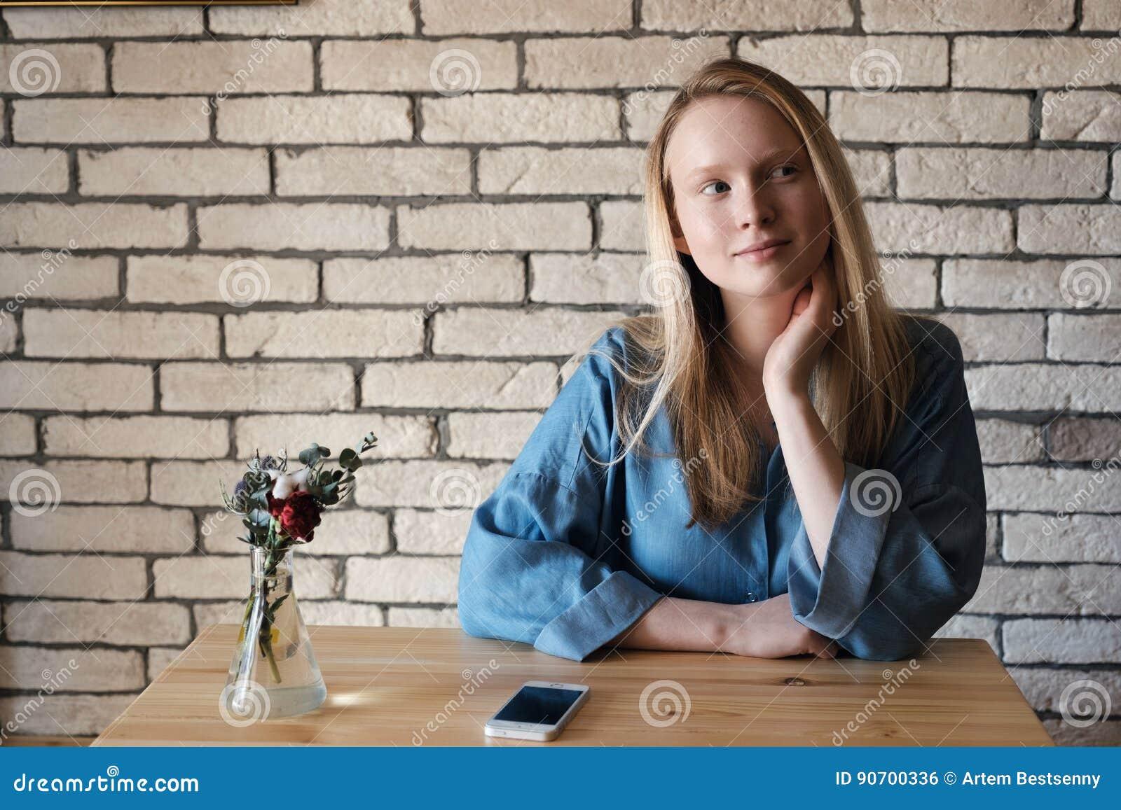 Den unga blondinen i blå skjorta sitter på en tabell i ett kafé som ligger på en telefon