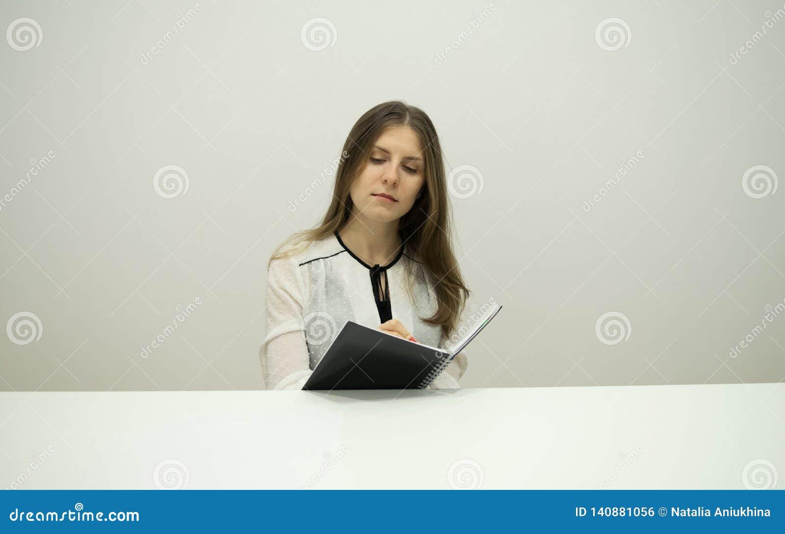 Den unga brunettflickan med flödande hår sitter på en tabell med en anteckningsbok i hennes händer