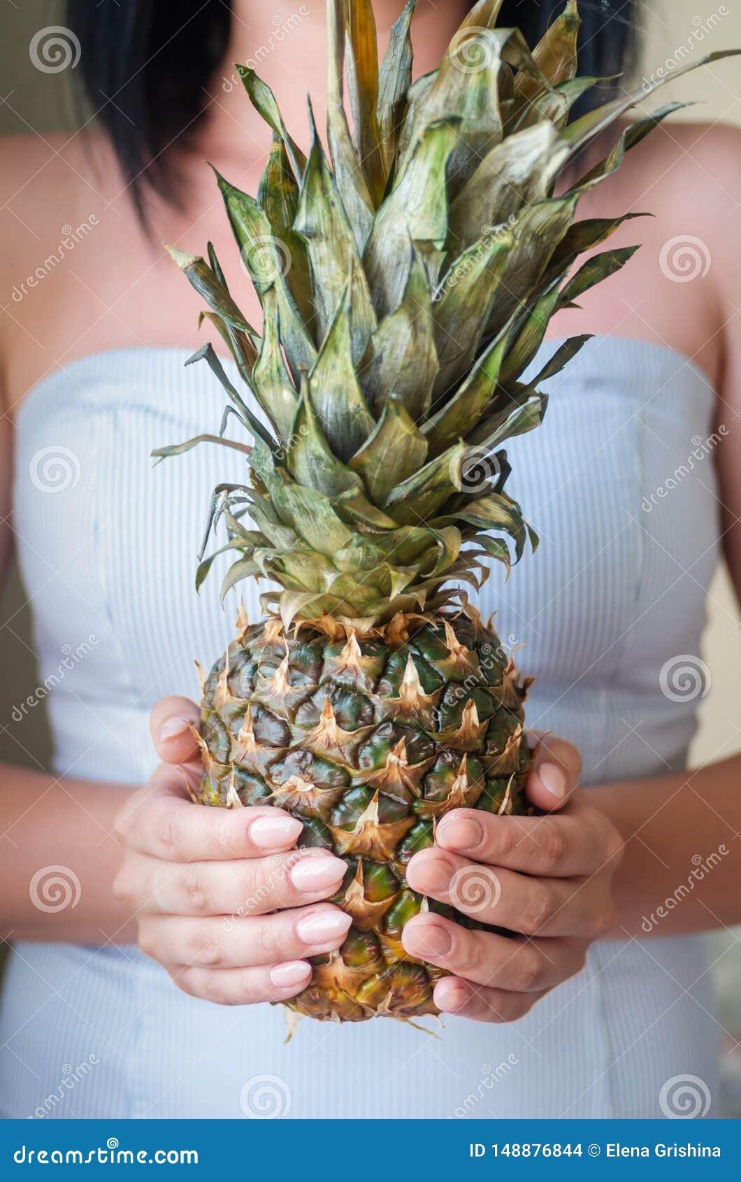 Den unga brunettflickan rymmer mogen ananas i hennes h?nder