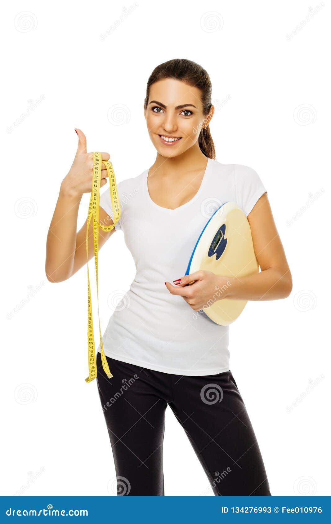 Den unga brunettkvinnan i det vita t-skjorta hållvåg och bandet ger upp tummar ställningar som poserar att le på vit bakgrund