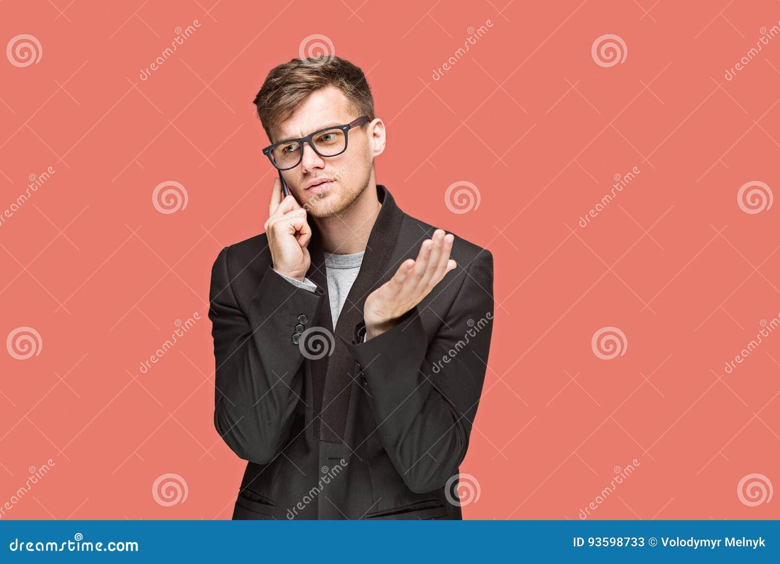 Den unga caucasian affärsmannen på röd bakgrund som talar på mobiltelefonen