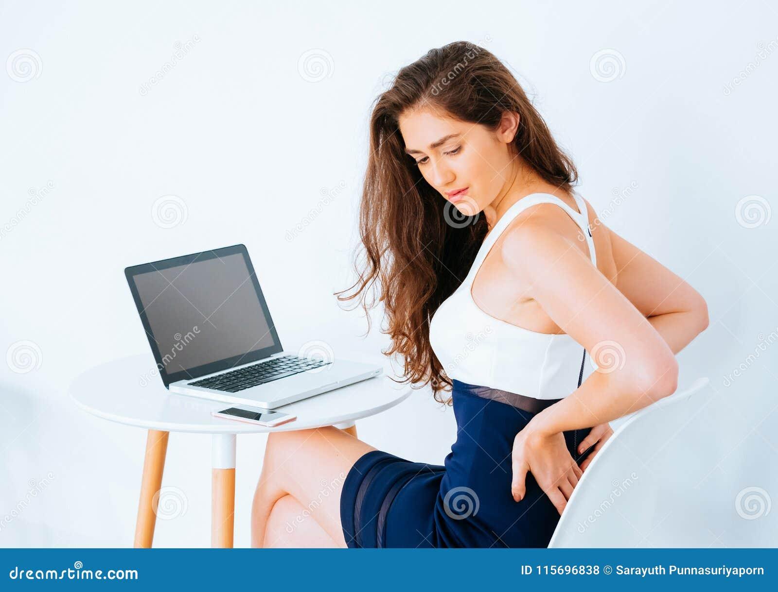 Den unga Caucasian funktionsdugliga affärskvinnan på skrivbordet med bärbara datorn som lider lägre baksida, och höften smärtar s