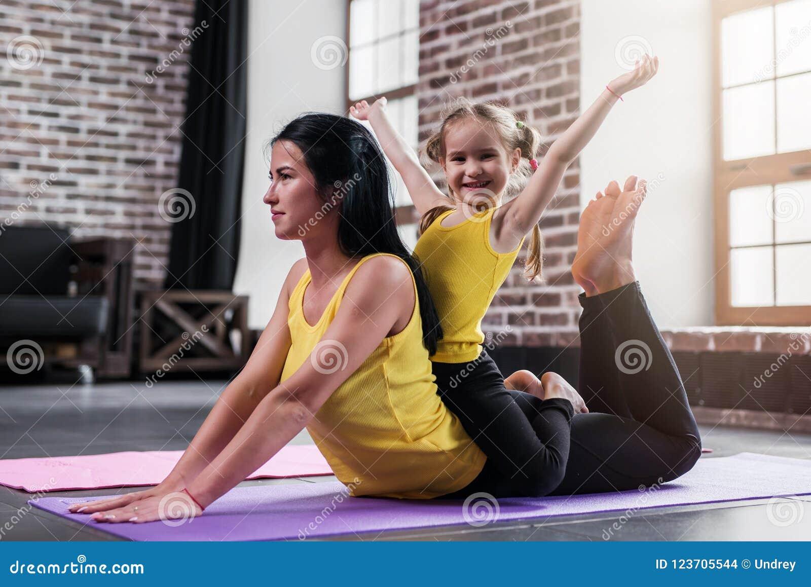 Den unga Caucasian modern som gör yogakobran, poserar på golv medan hennes le dottersammanträde på mammor tillbaka
