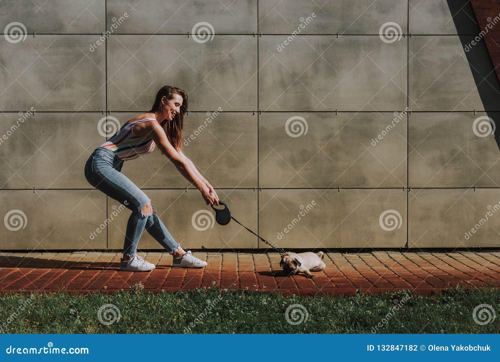 Den unga damen drar på koppeln hennes lilla valp