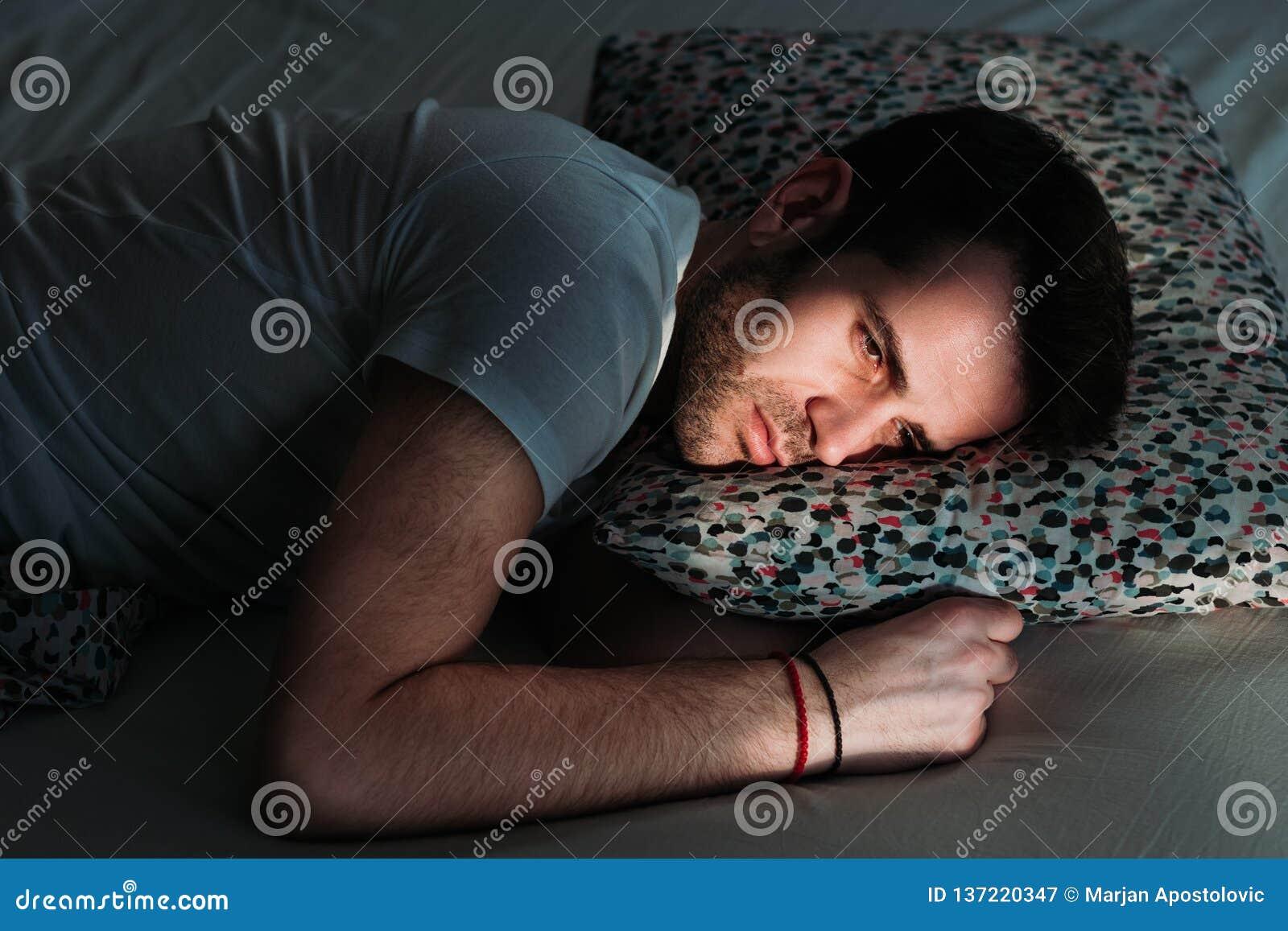 Den unga deprimerade mannen smärtar in på sängen