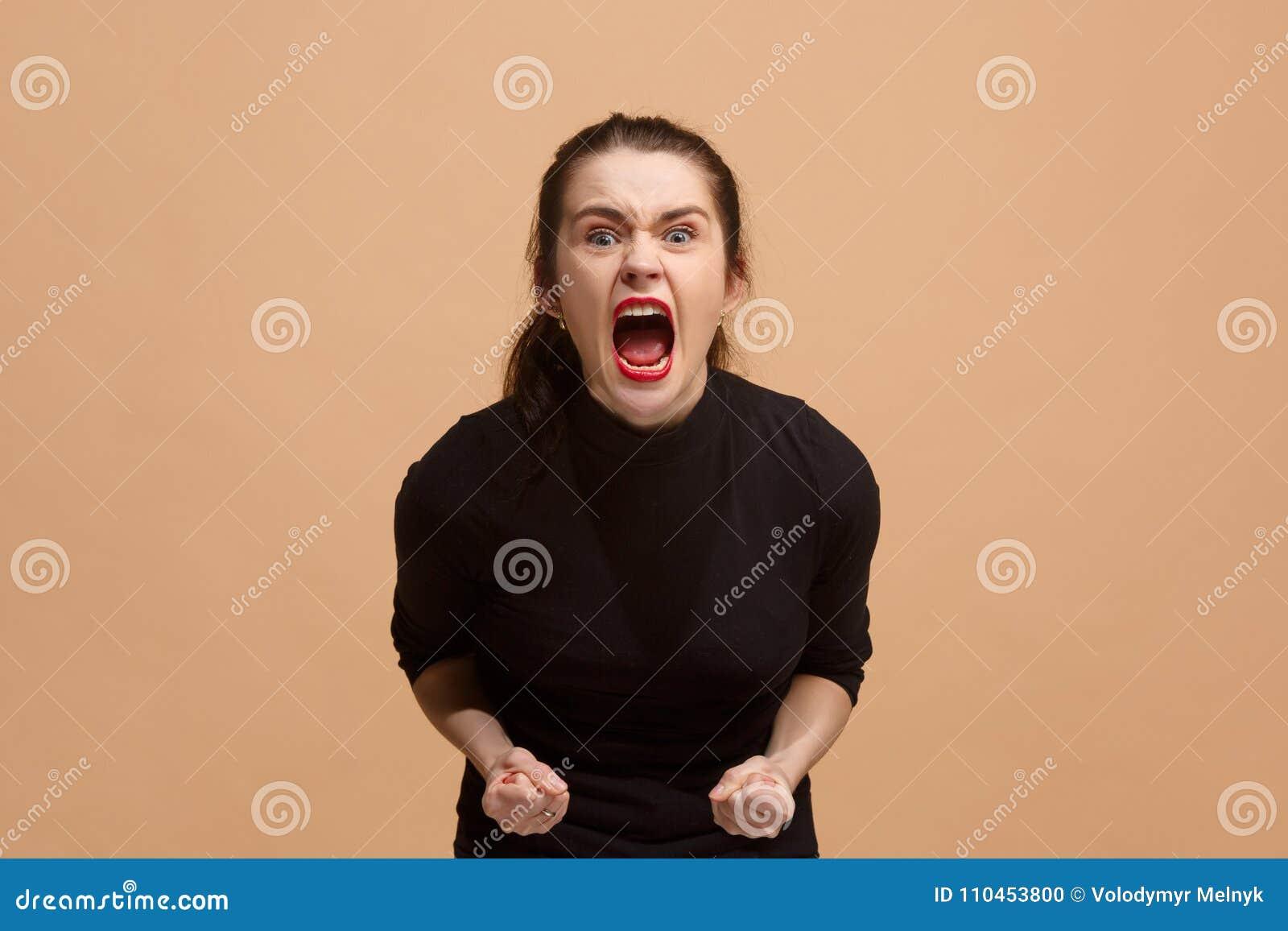 Den unga emotionella ilskna kvinnan som skriker på pastellfärgad studiobakgrund