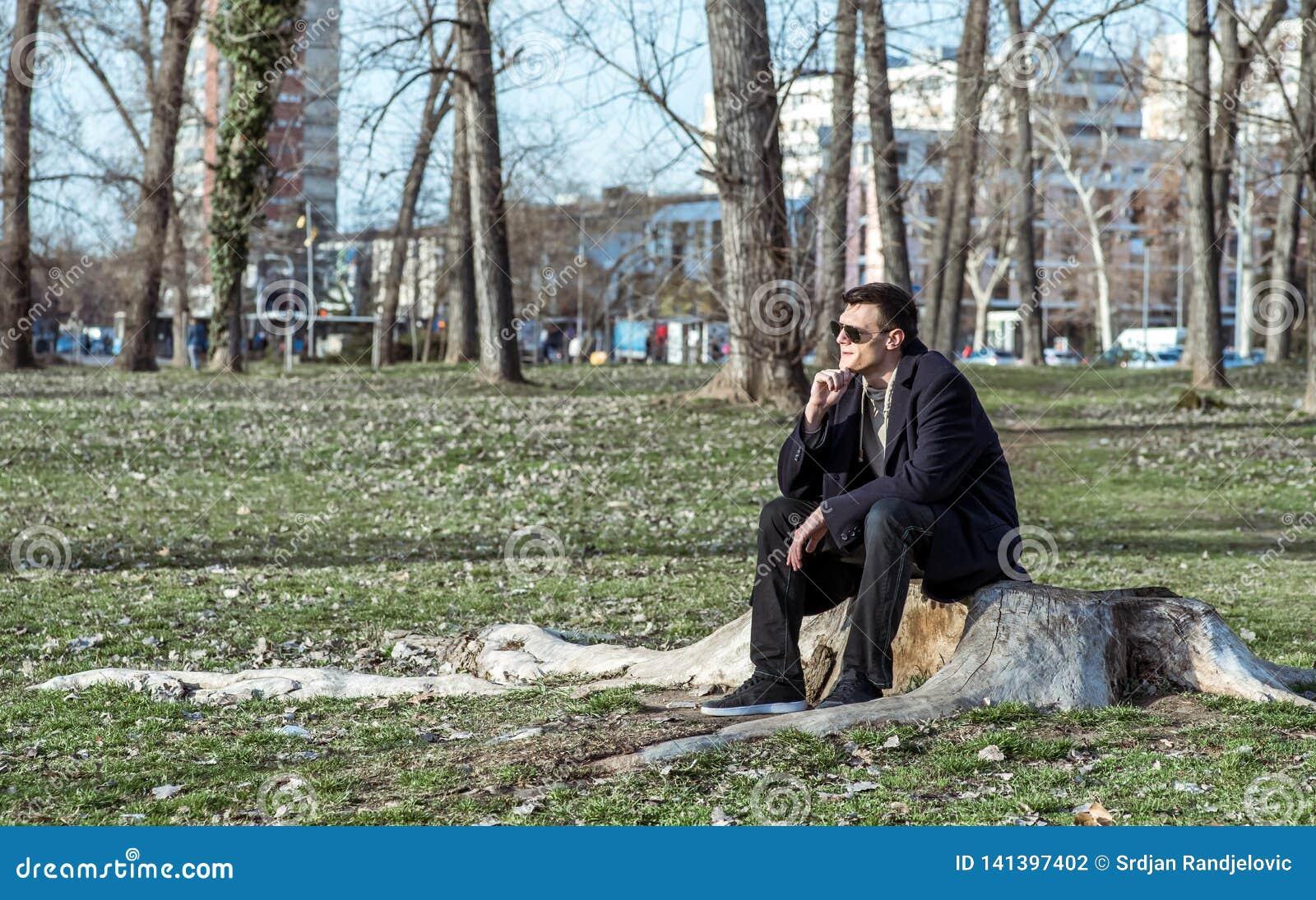 Den unga ensamma deprimerade och angelägna mannen som bara sitter i, parkerar på trästubben som svikas i hans liv som gråter och