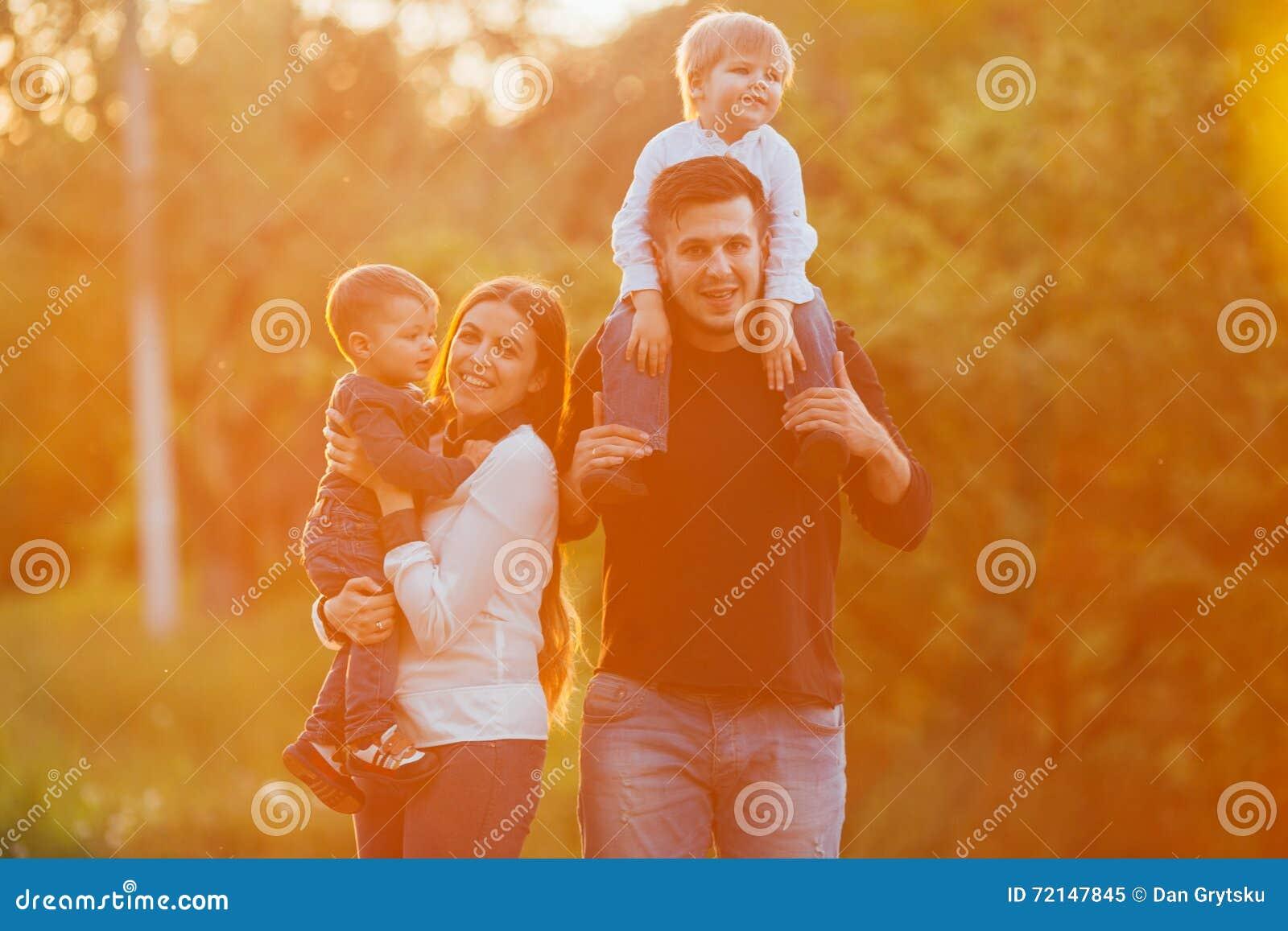 Den unga familjen med barn som in går, parkerar Fader, moder och två söner