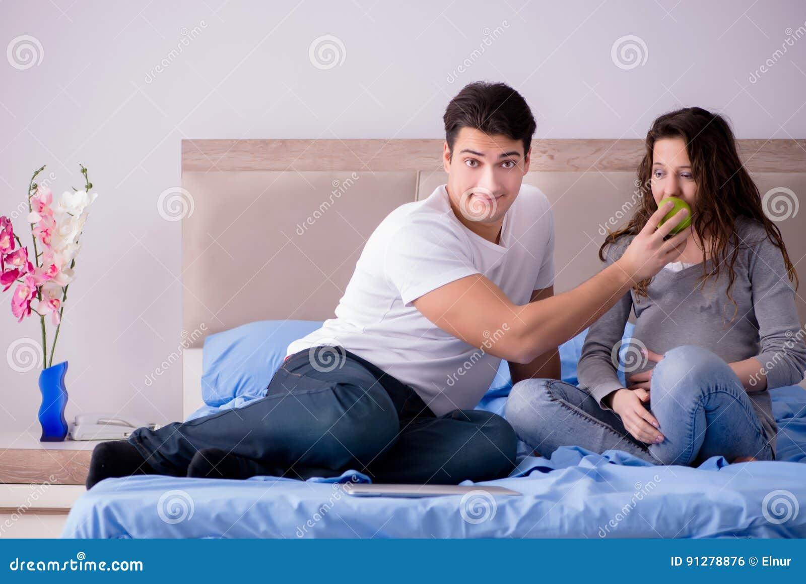 Den unga familjen med den gravida frun som förväntar, behandla som ett barn i säng