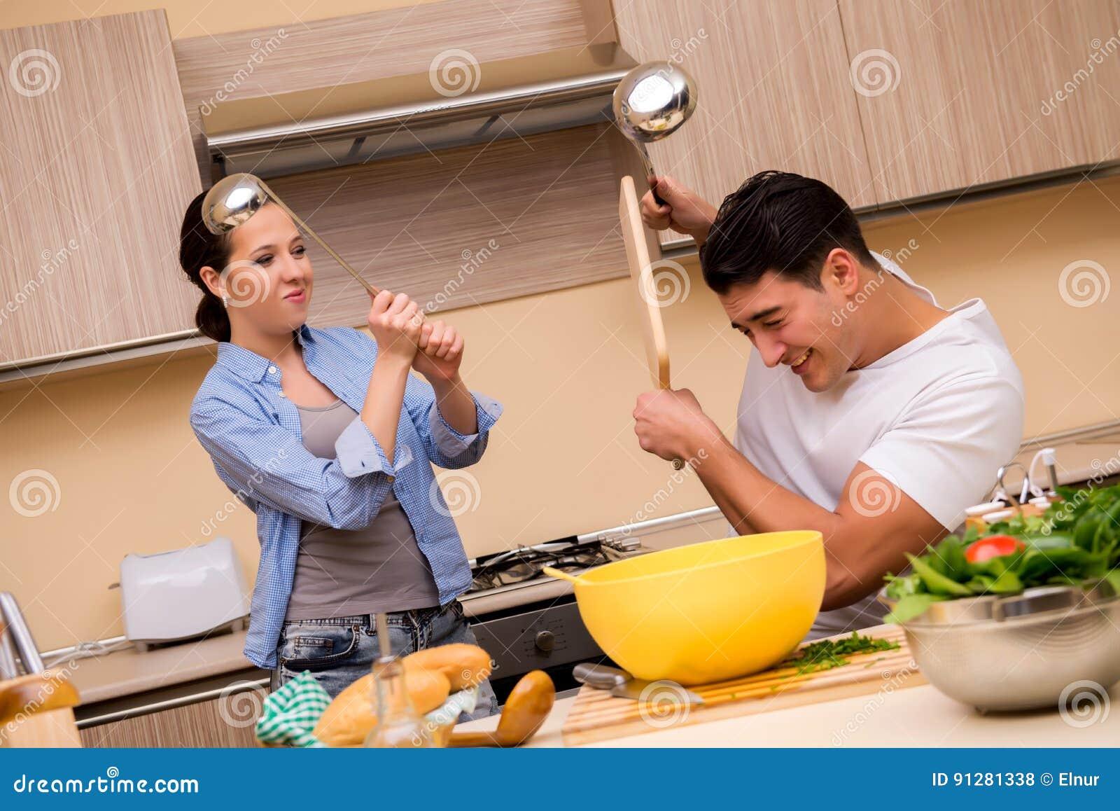 Den unga familjen som gör rolig kamp på kök