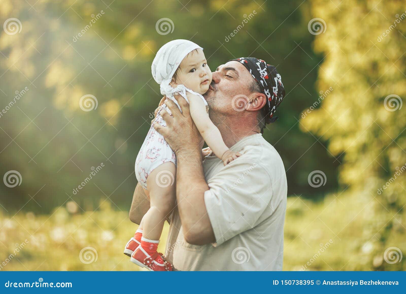 Den unga farfadern som spelar med förtjusande, behandla som ett barn flickan över en naturbakgrund Morföräldrar och barnbarnfriti