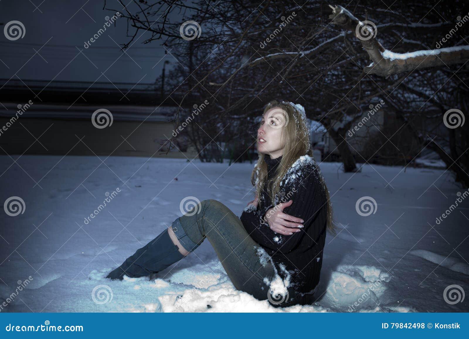 Den unga fryste kvinnan under den fallande snön