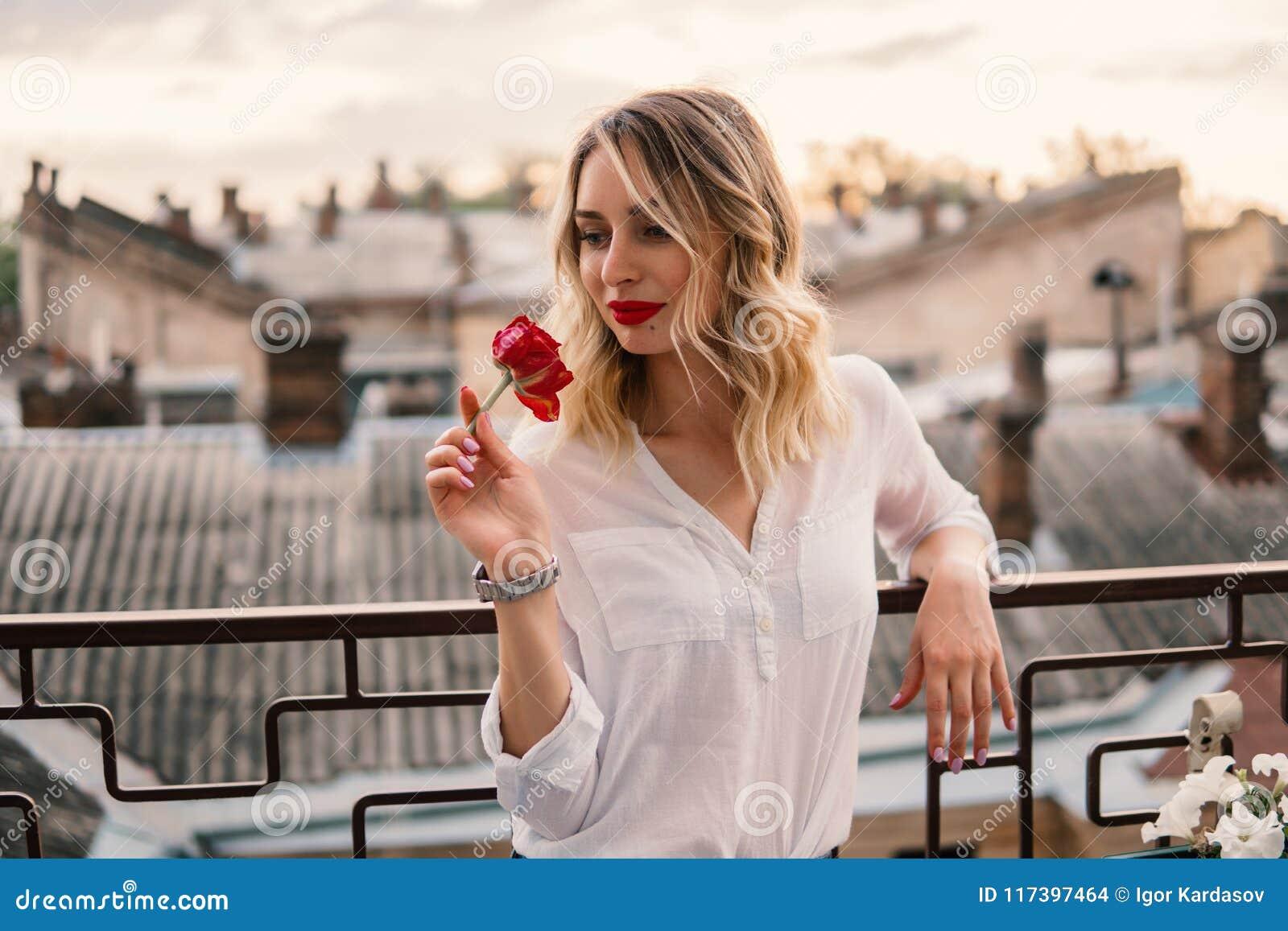 Den unga gladlynta flickan rymmer den röda blomman på balkong eller taket
