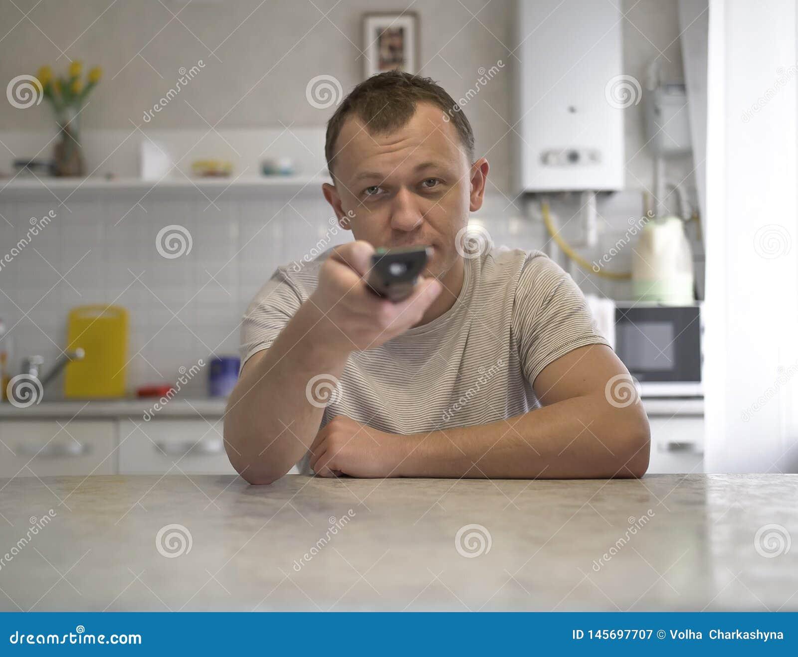 Den unga grabben med en TVfjärrkontroll kopplar kanaler, medan sitta i köket, främre sikt