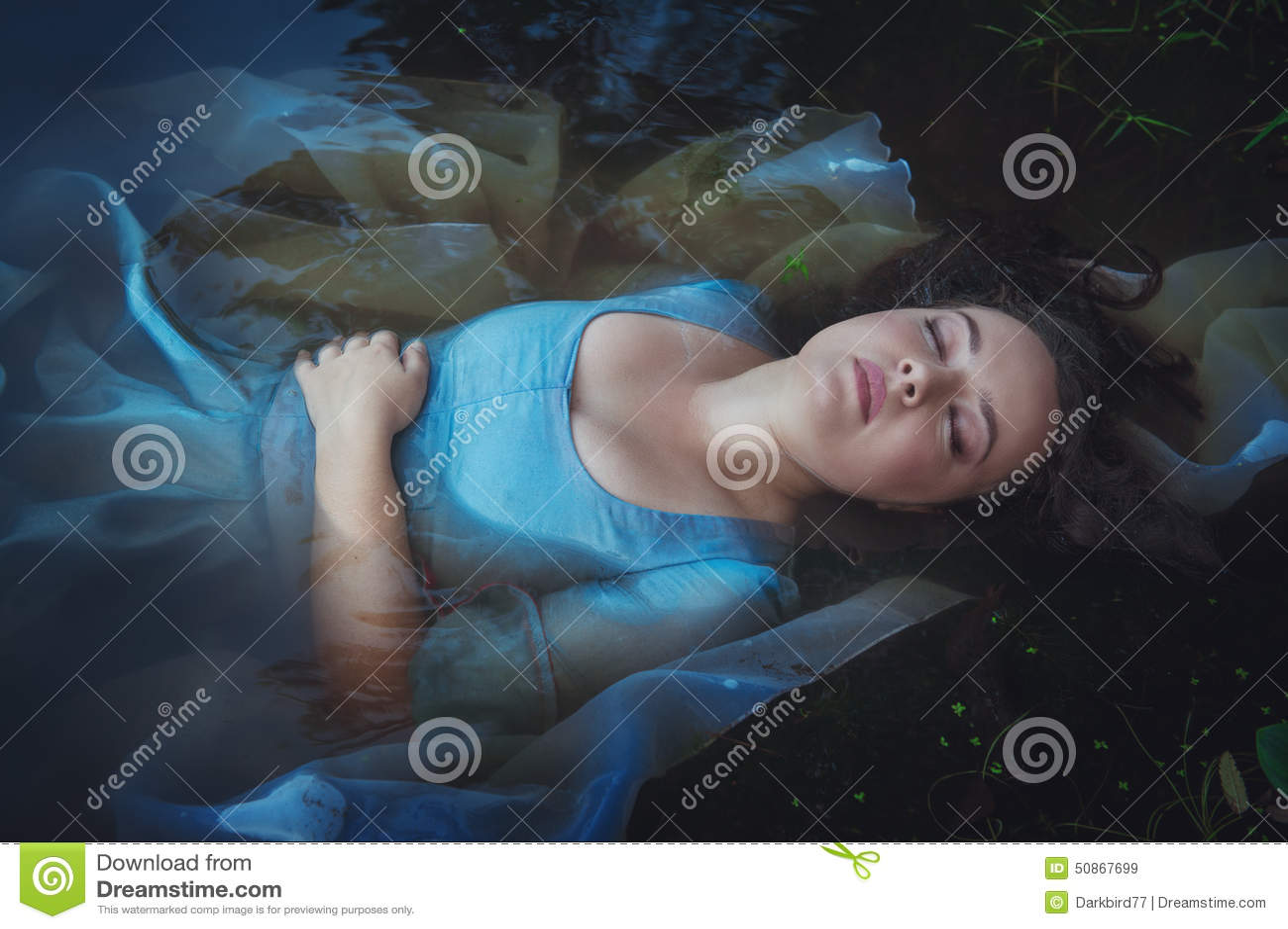 Den unga härliga drunknade kvinnan i blått klär att ligga i floden