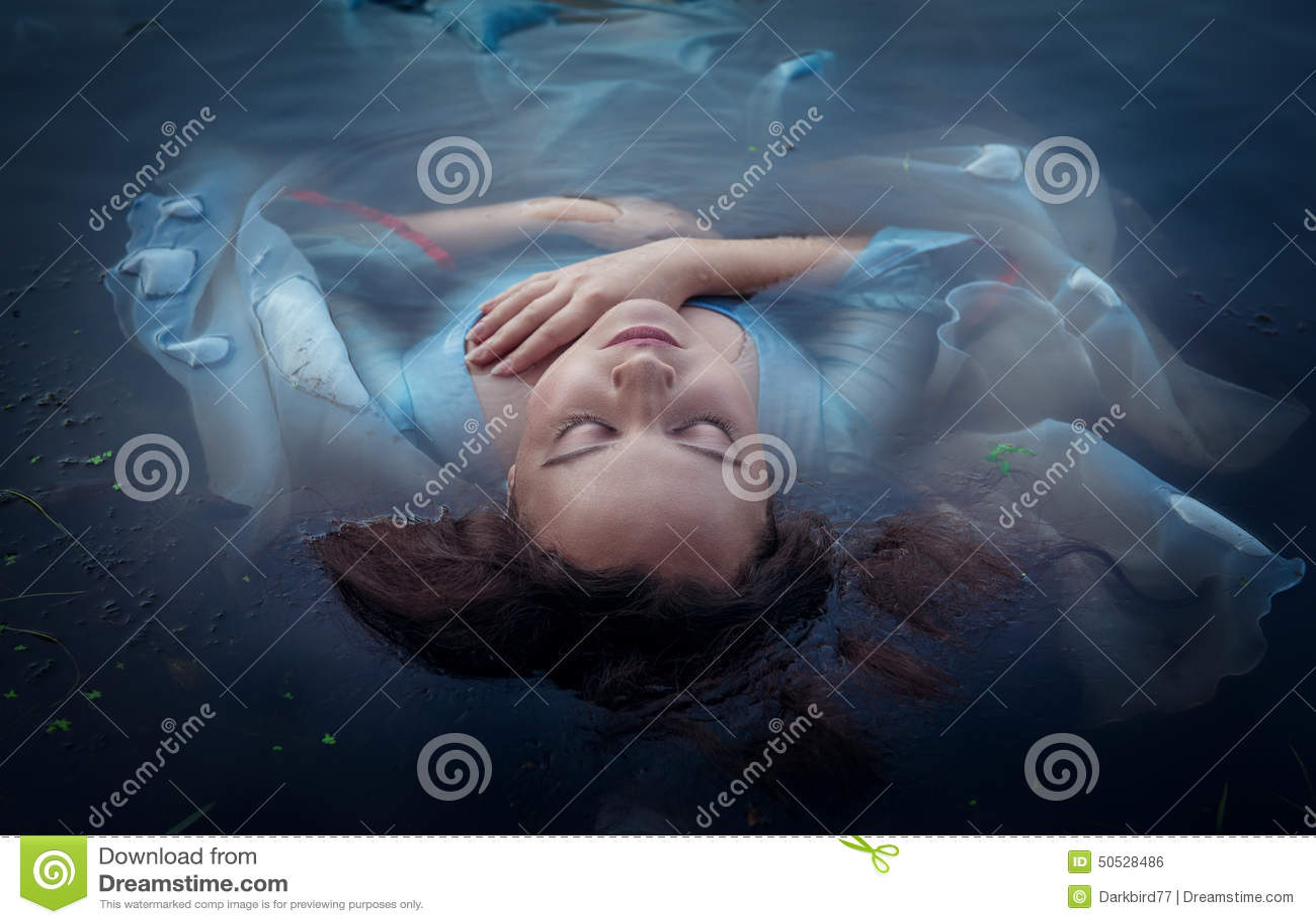 Den unga härliga drunknade kvinnan i blått klär att ligga i vattnet