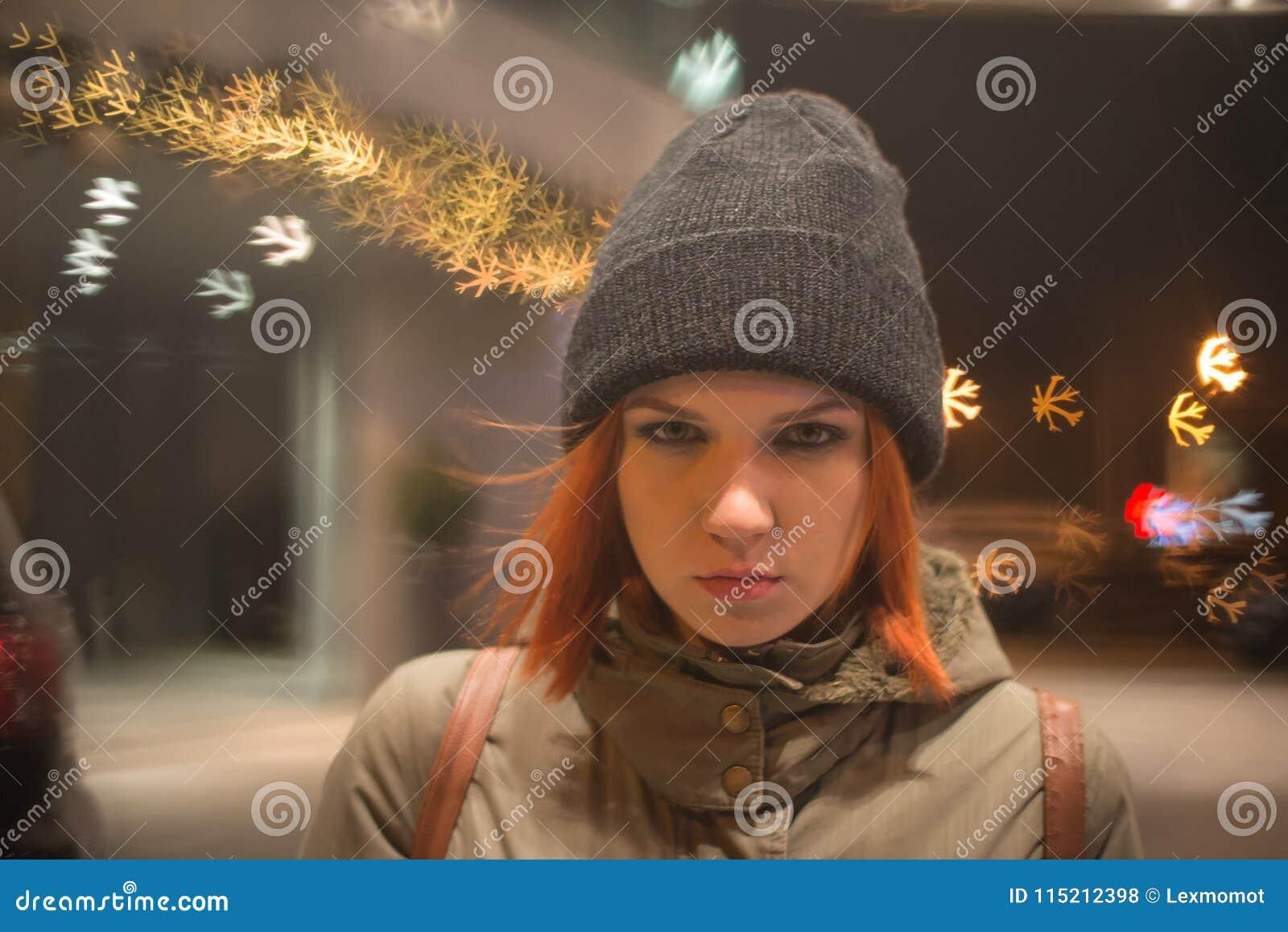 Den unga härliga flickan fångar en taxi i stadsgatan på natten
