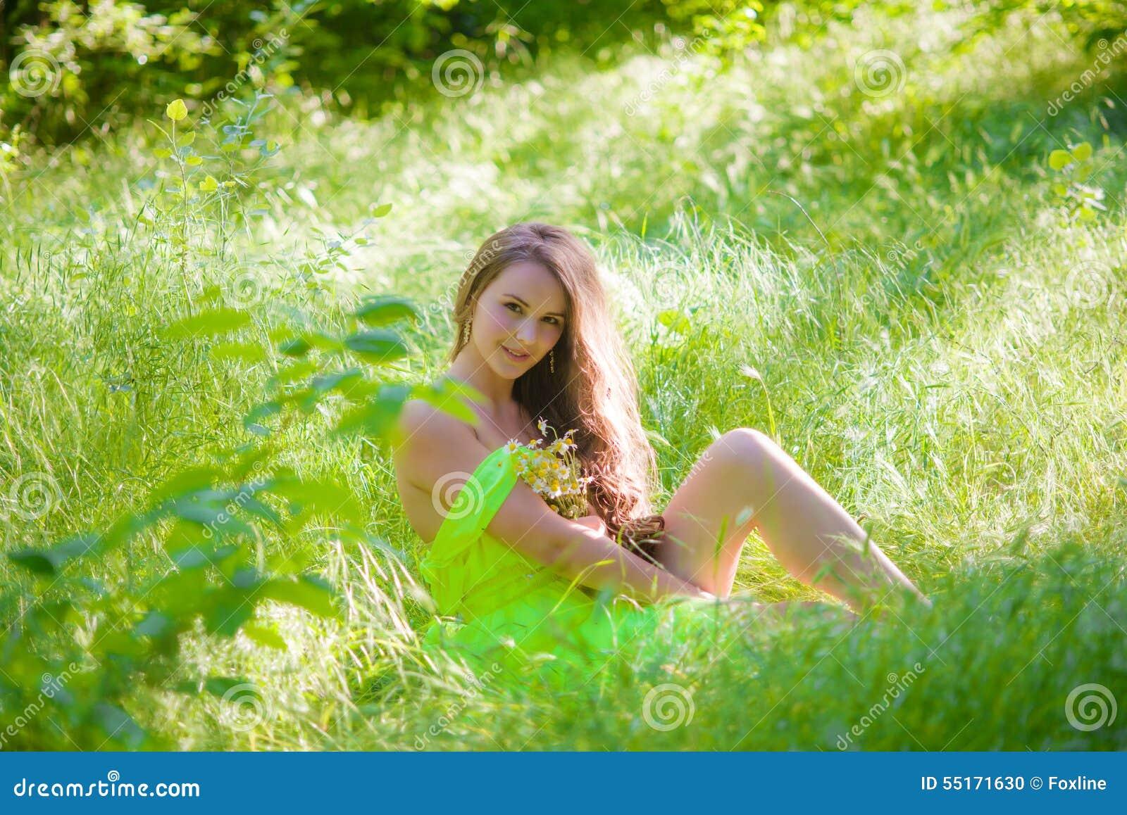 Den unga härliga flickan med långt hår i en ljus klänning