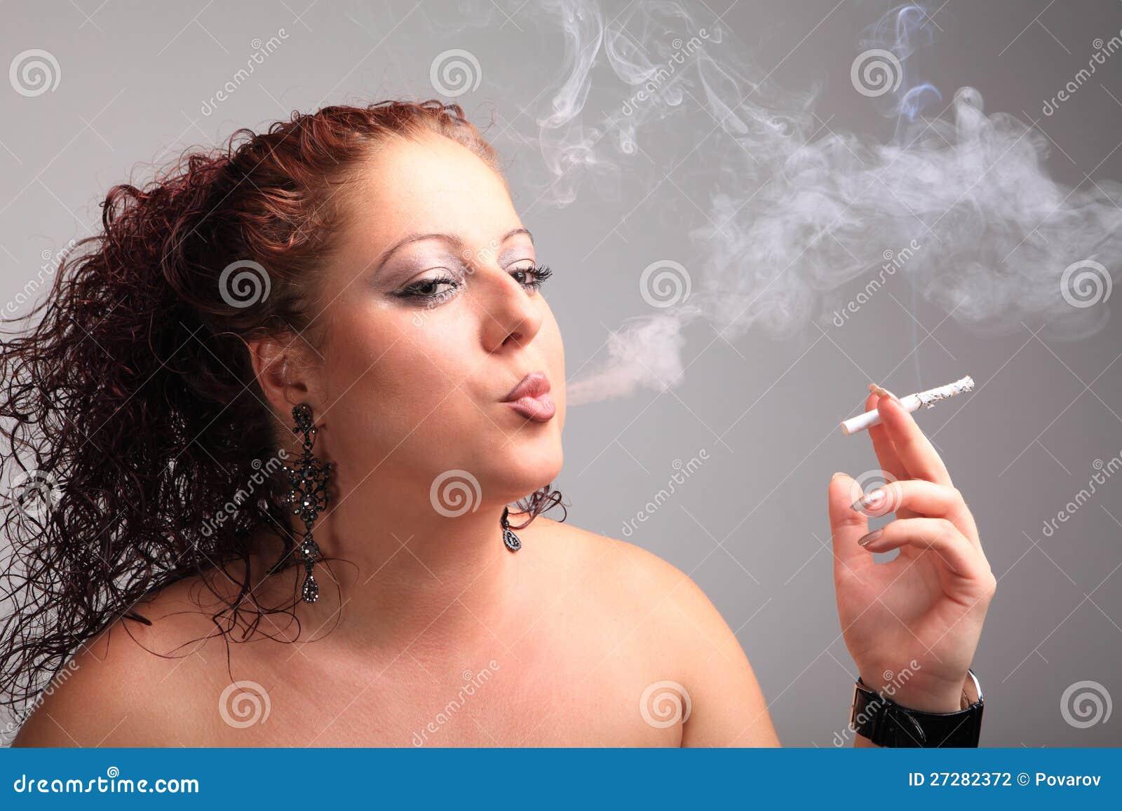 Den unga härliga flickan röker en cigarett