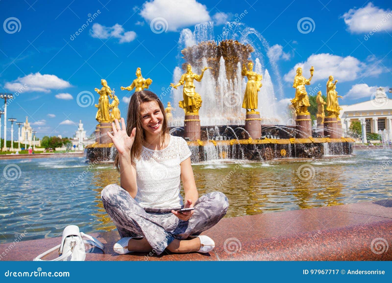 Den unga härliga kvinnan har ett vilasammanträde nära springbrunnen