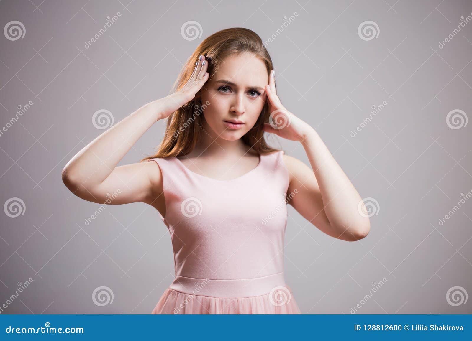 Den unga härliga kvinnan har huvudvärken som isoleras på grå bakgrund
