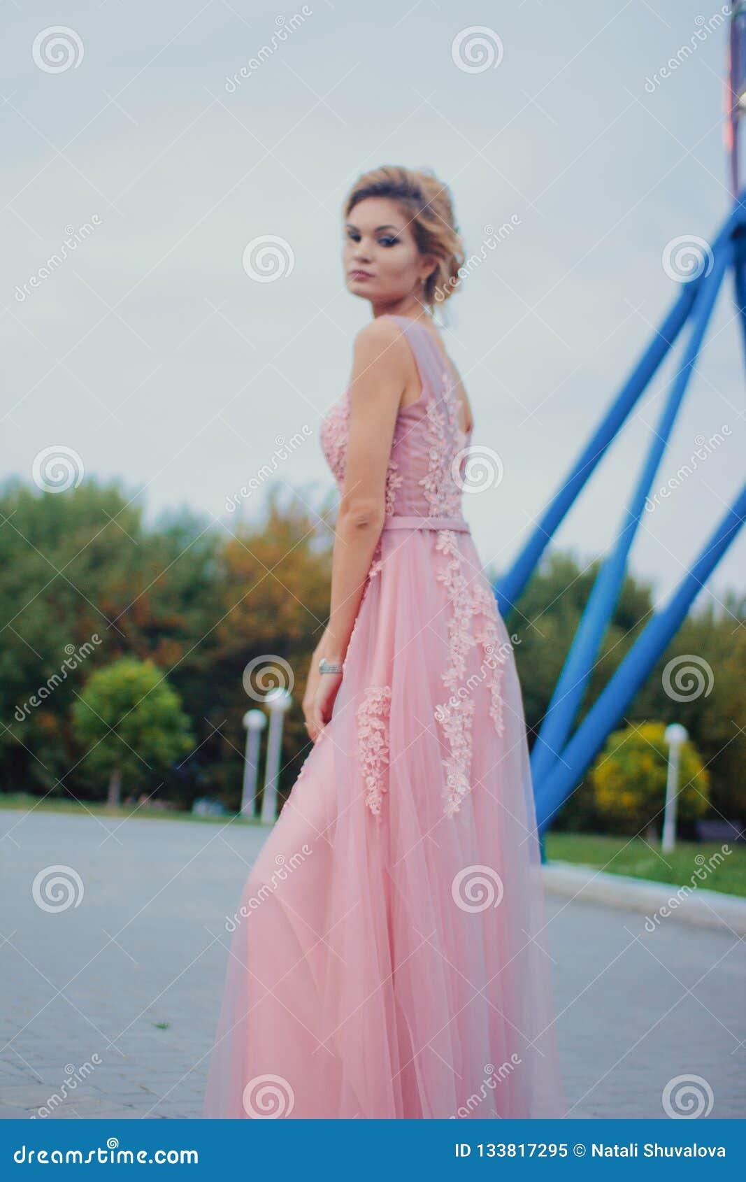 Den unga härliga kvinnan i lång rosa gå bana för aftonklänning parkerar in Dana stilståenden av den ursnygga härliga flickan utom