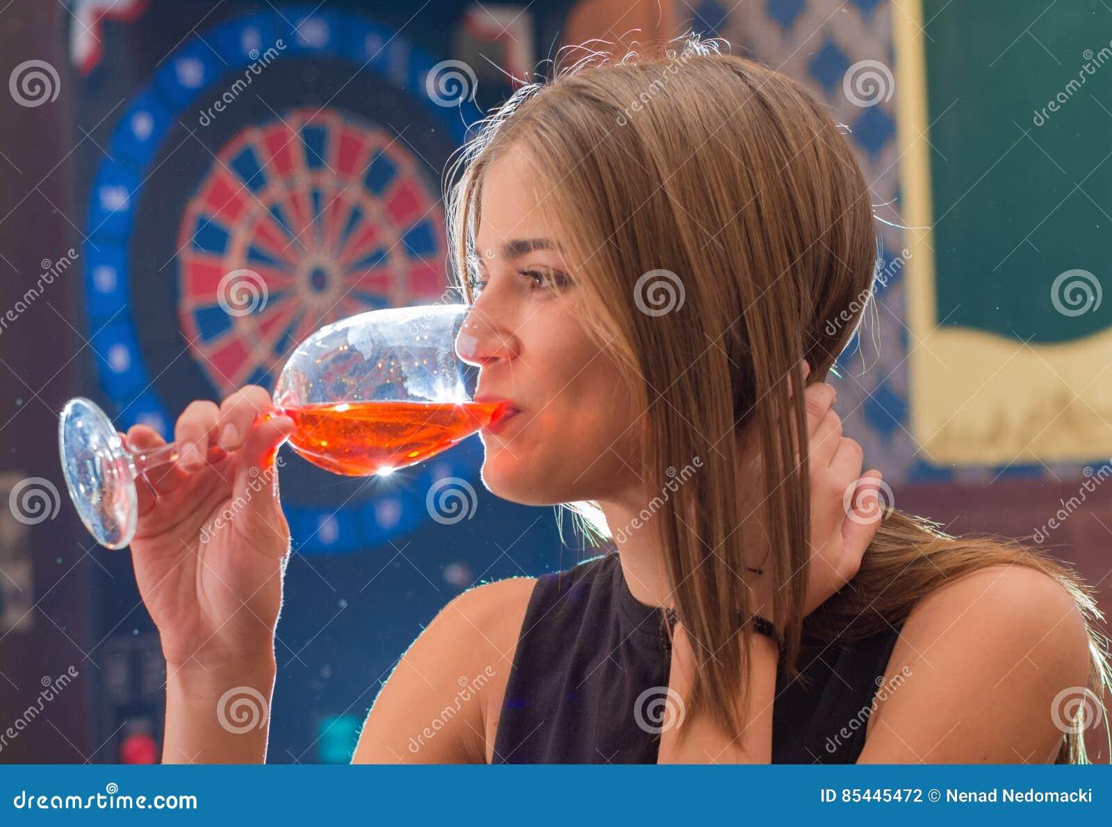Den unga härliga kvinnan kopplar av i nattklubb