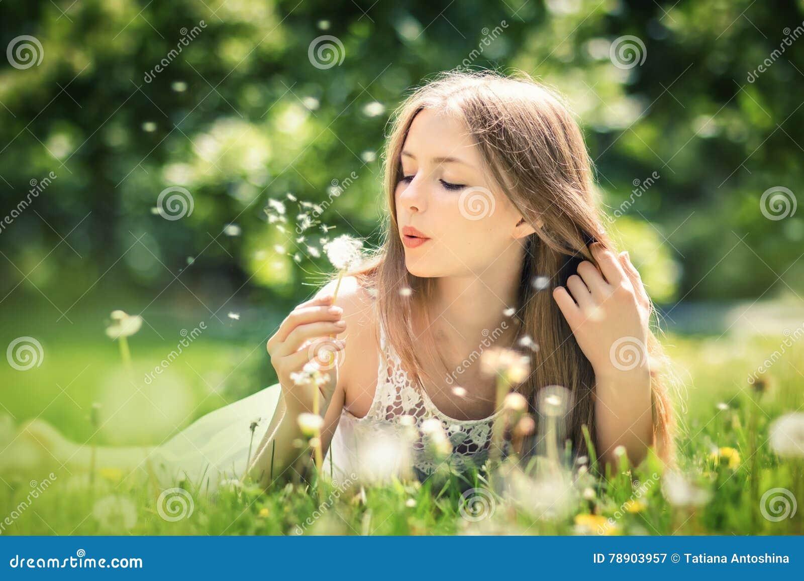 Den unga härliga kvinnan ligger på ett gräs