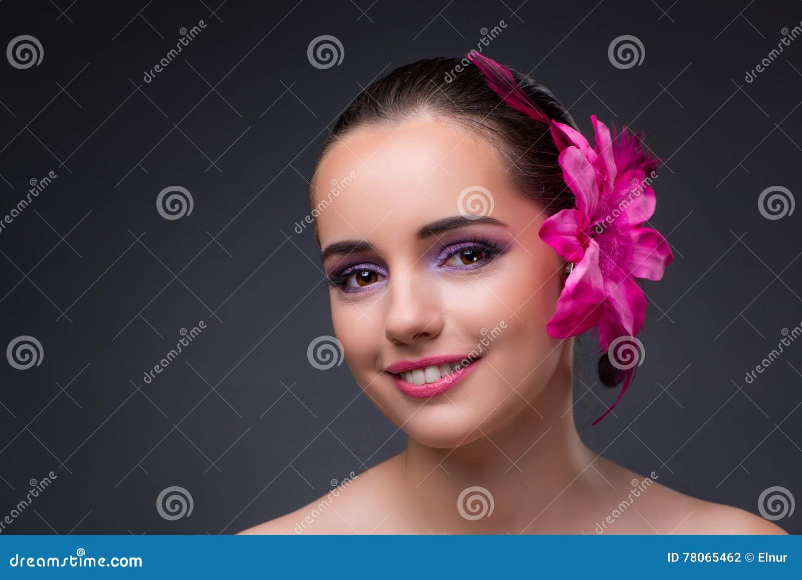 Den unga härliga kvinnan med orkidéblomman
