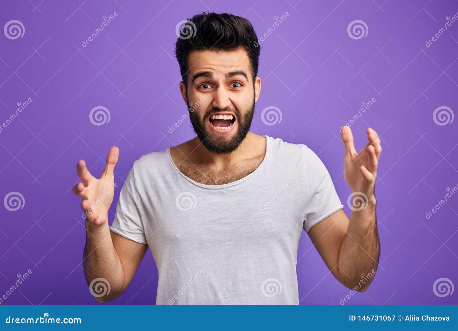 Den unga ilskna skäggiga mannen uttrycker hans negativa sinnesrörelser