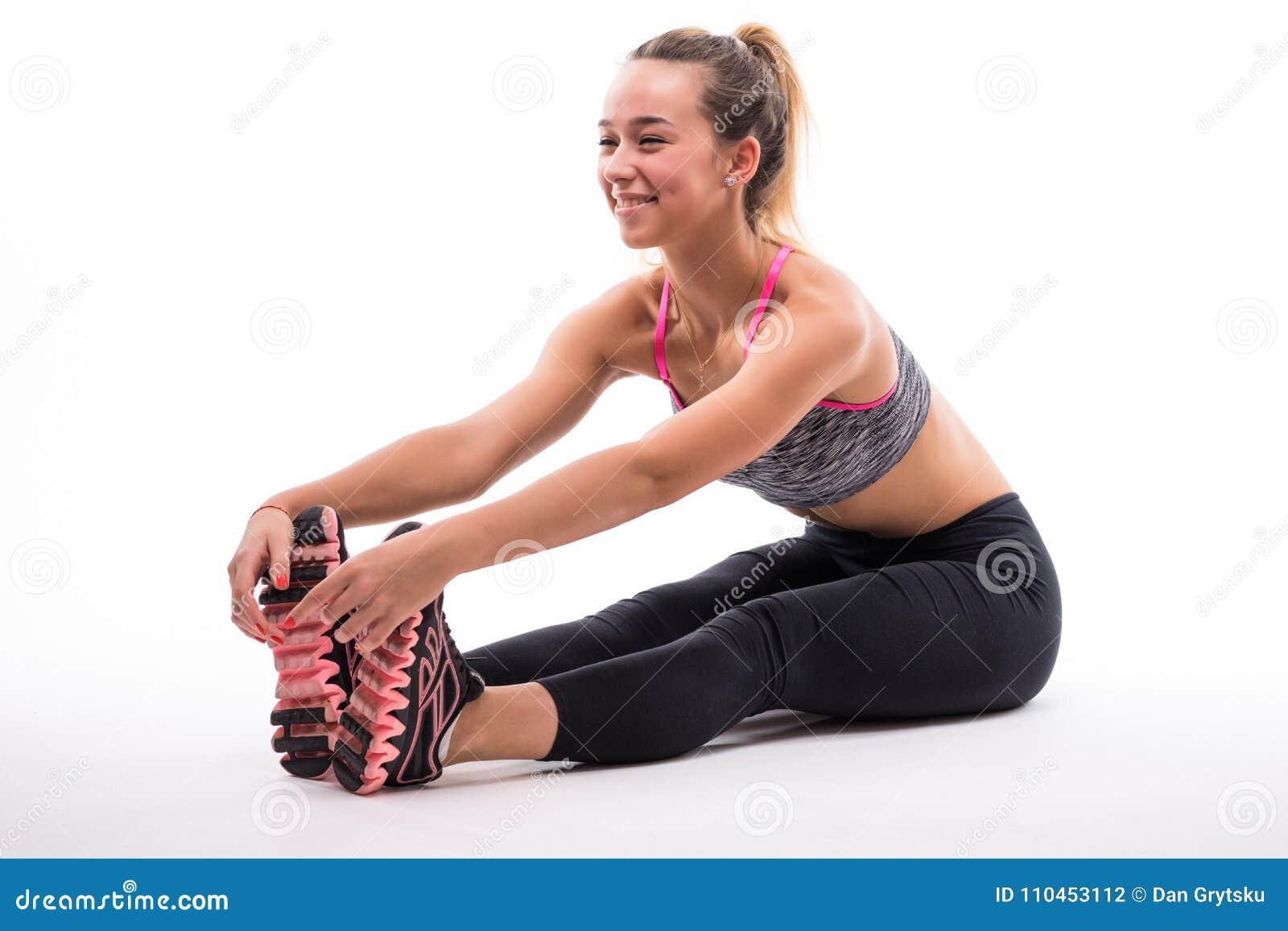 Den unga konditionmodellen i den vita sportswearen som gör yoga eller pilates som utbildar, den placerade framåt krökningen, pose